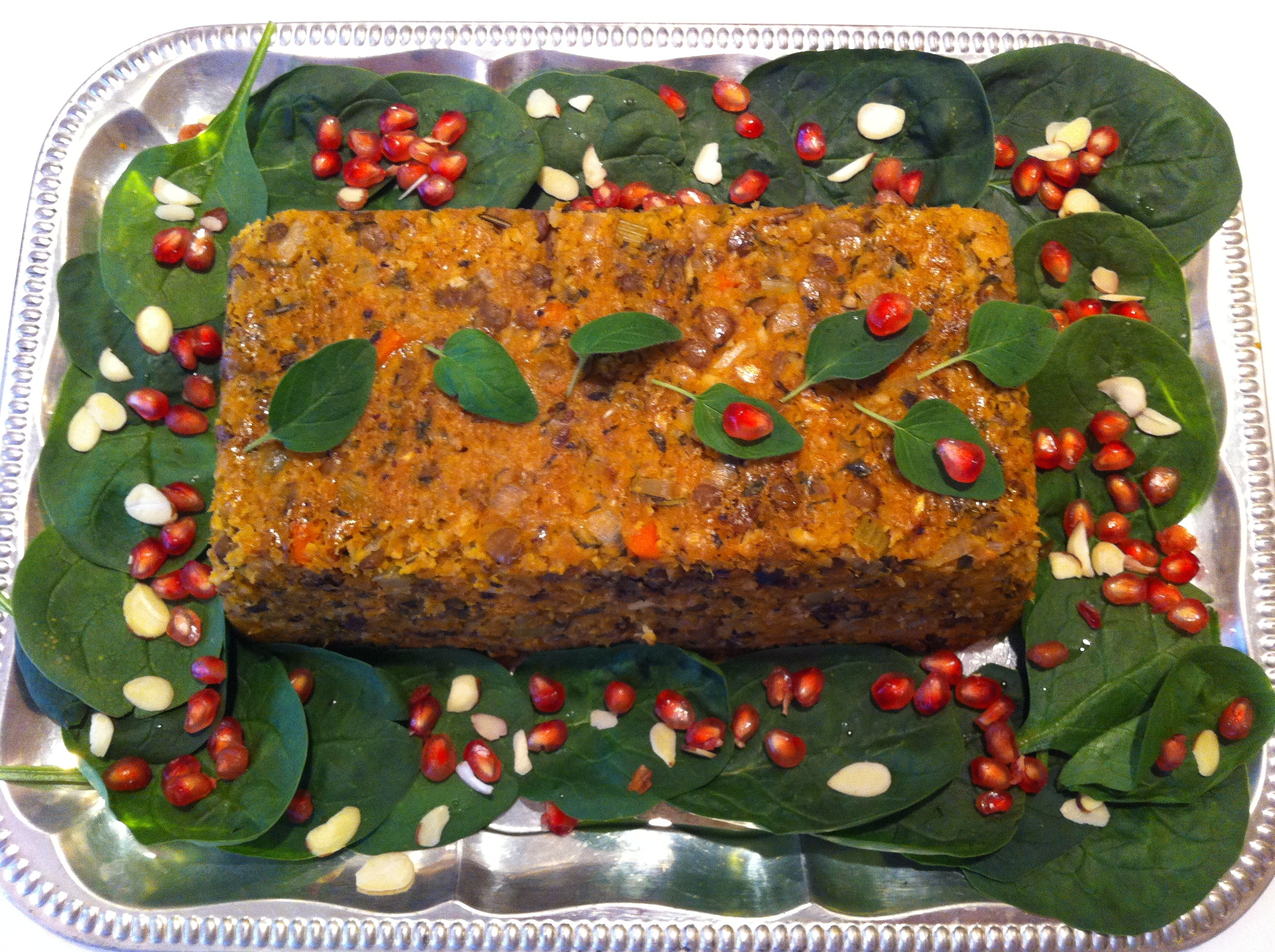 <p>A holiday lentil loaf on a bed of spinach with pomegranate seeds</p>