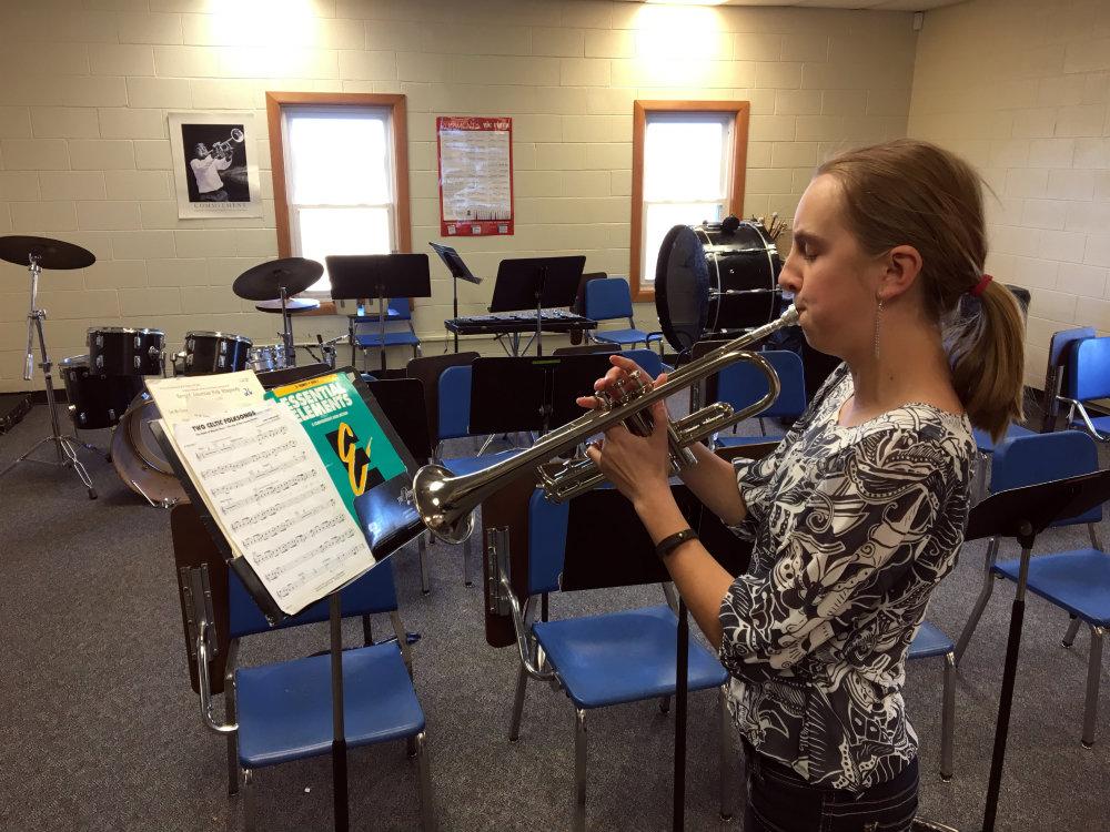 <p>Seventh grader Maggie Reid plays her trumpet in the band room in Karval School.</p>