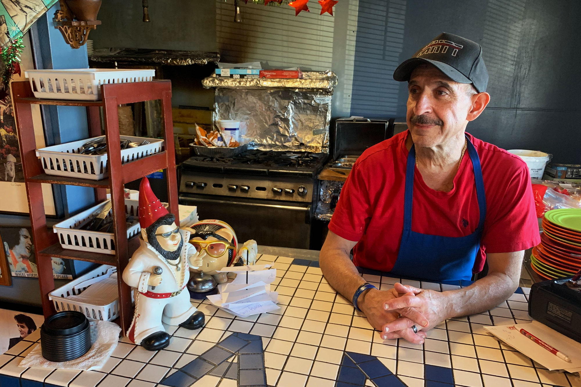 <p>Nick Andurlakisat the counter of his Elvis-themed restaurant, Nick's Cafe, located near a hub offederal agency in Lakewood. Andurlakissaid the cafe has lost 20 or 25 percent of its business during the shutdown.</p>