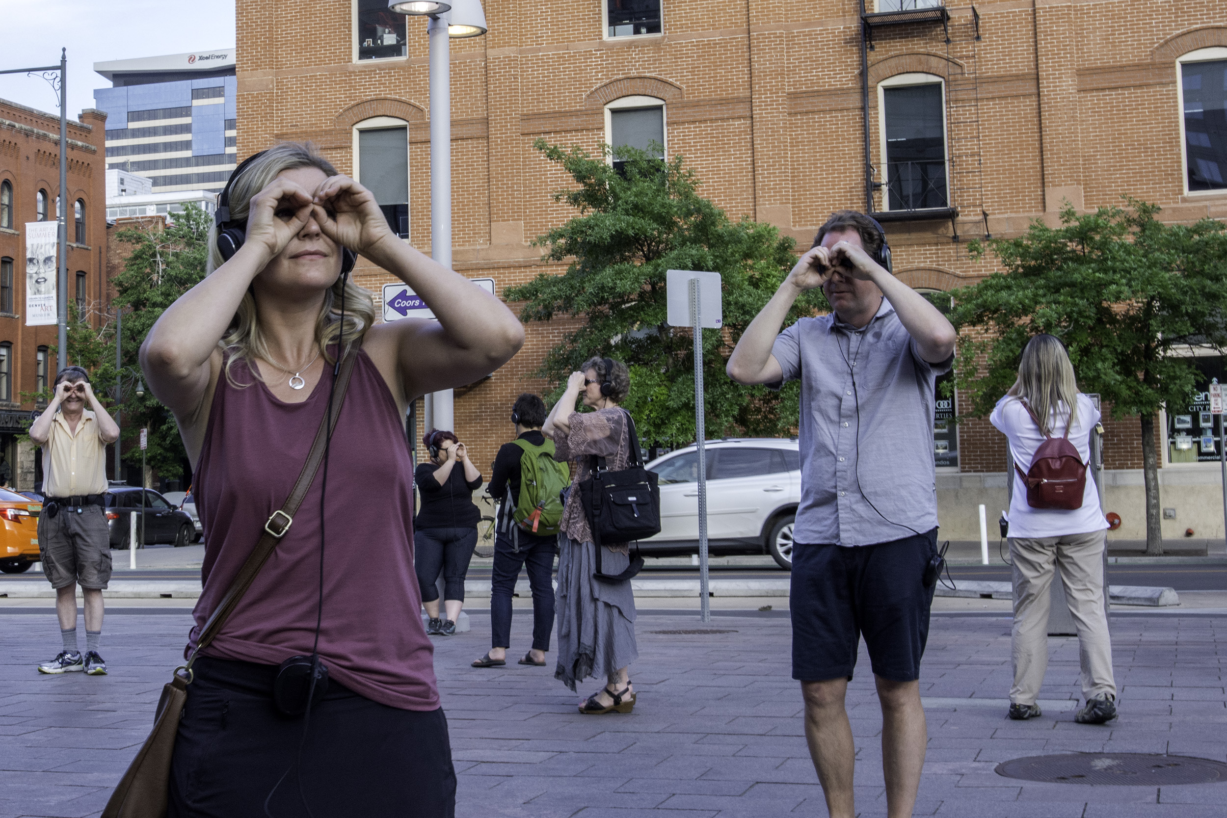 "<p>""Remote Denver"" participants use their hands to mimic binoculars while touring outside Denver's Union Station on Tuesday, June 12, 2018. </p>"
