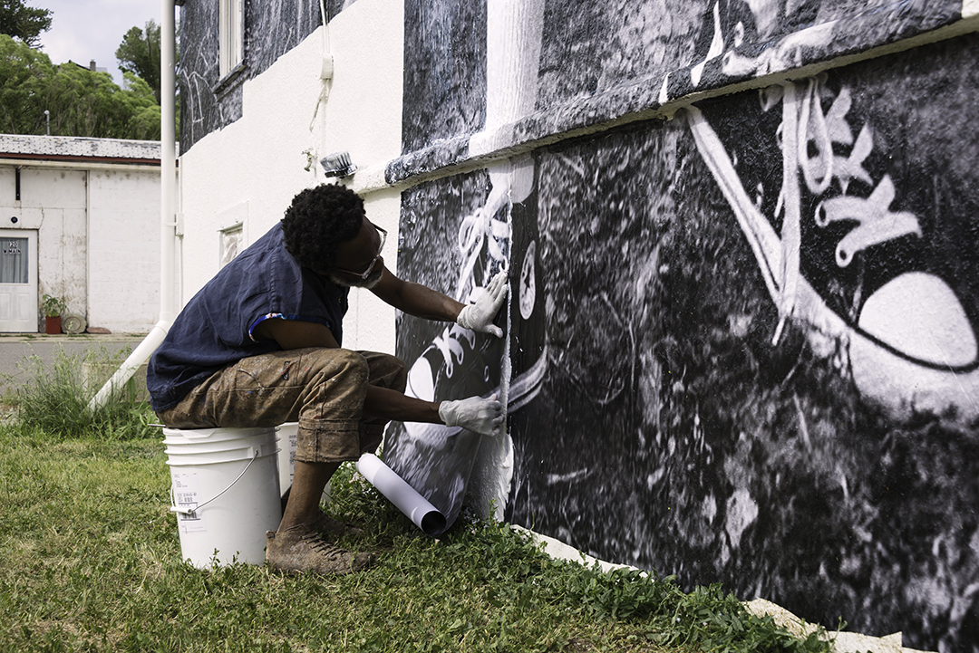 Photo: Chip Thomas works on mural photo in Hotchkiss
