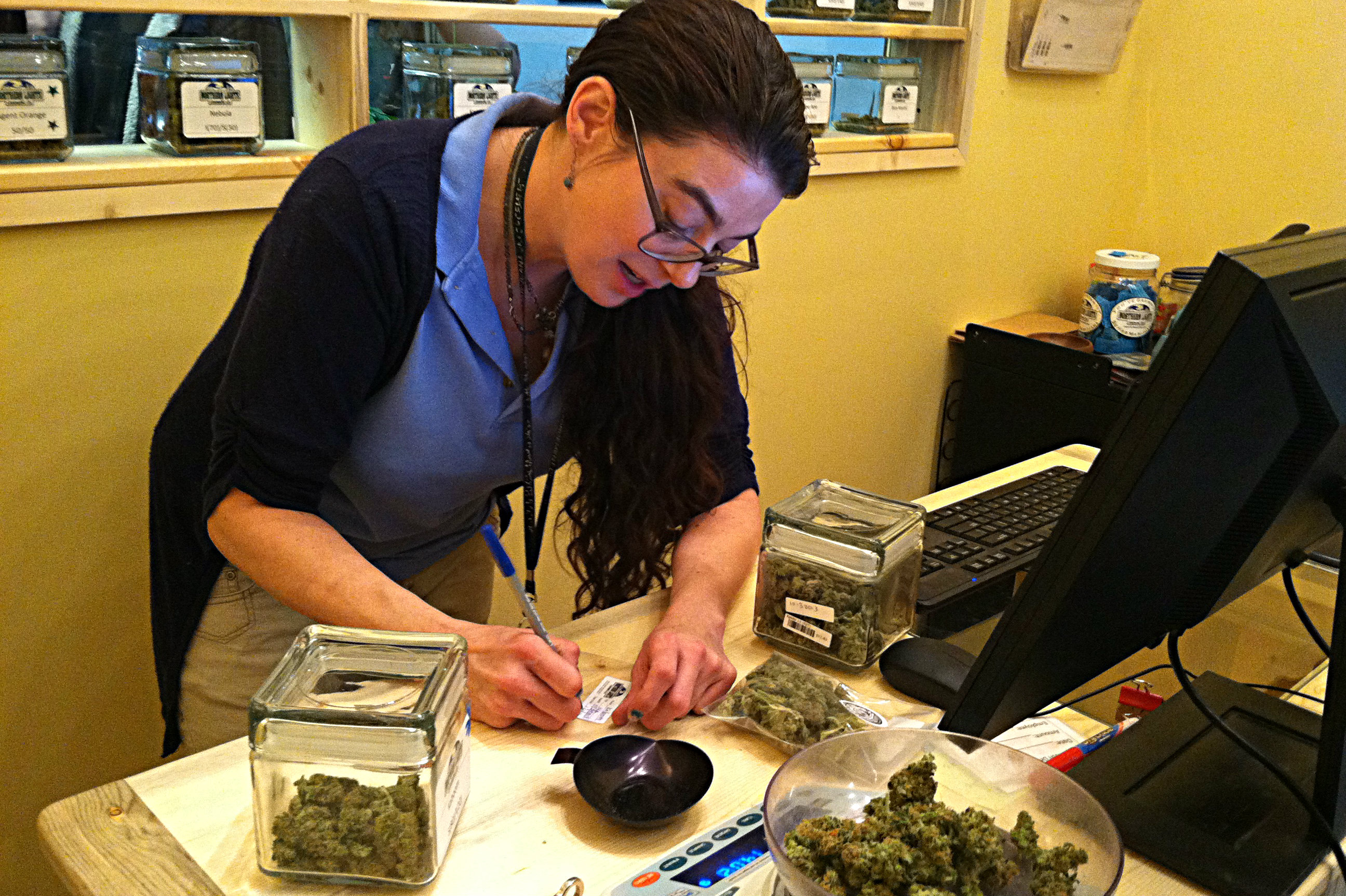 <p>A bud tender at Northern Lights packages product for a customer. In the jars on the shelves behind her, the buds for sale to recreational users are kept separate from marijuana intended for medical smokers, as is required by state law. </p>