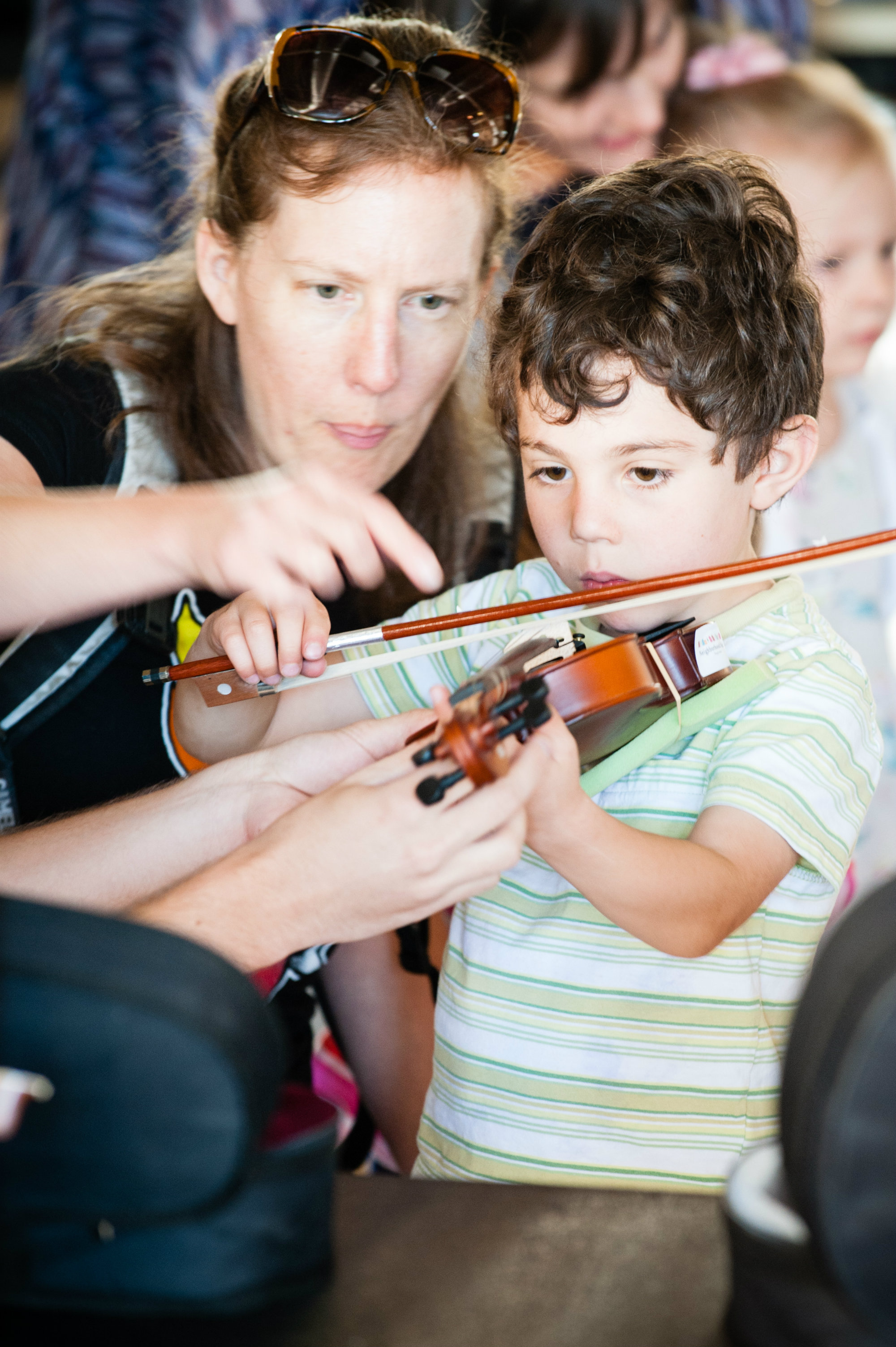 <p>An impromptu violin lesson at Inside the Orchestra's instrument petting zoo.</p>