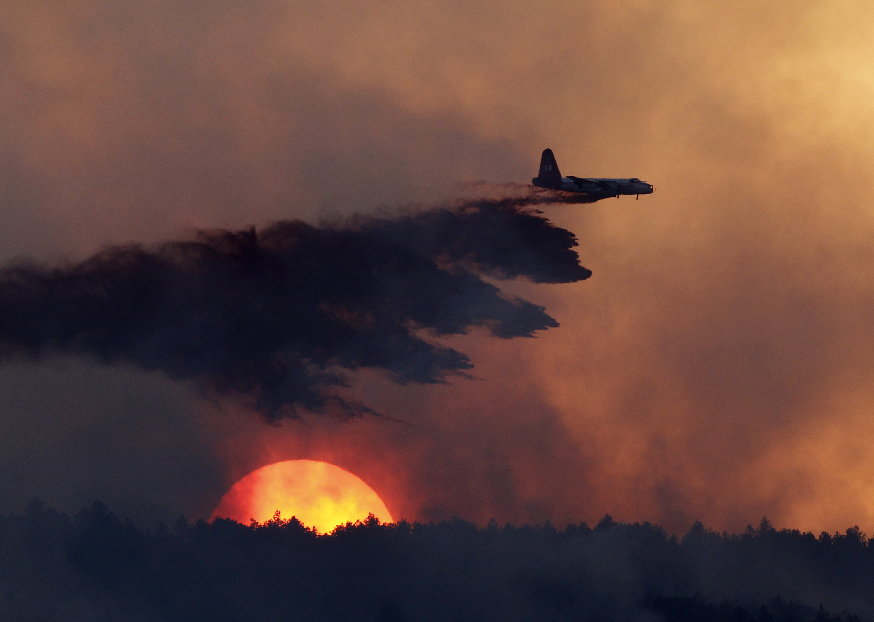 Photo: Wildfire slurry bomber at sunset, Loveland, Colo 2010 (AP)