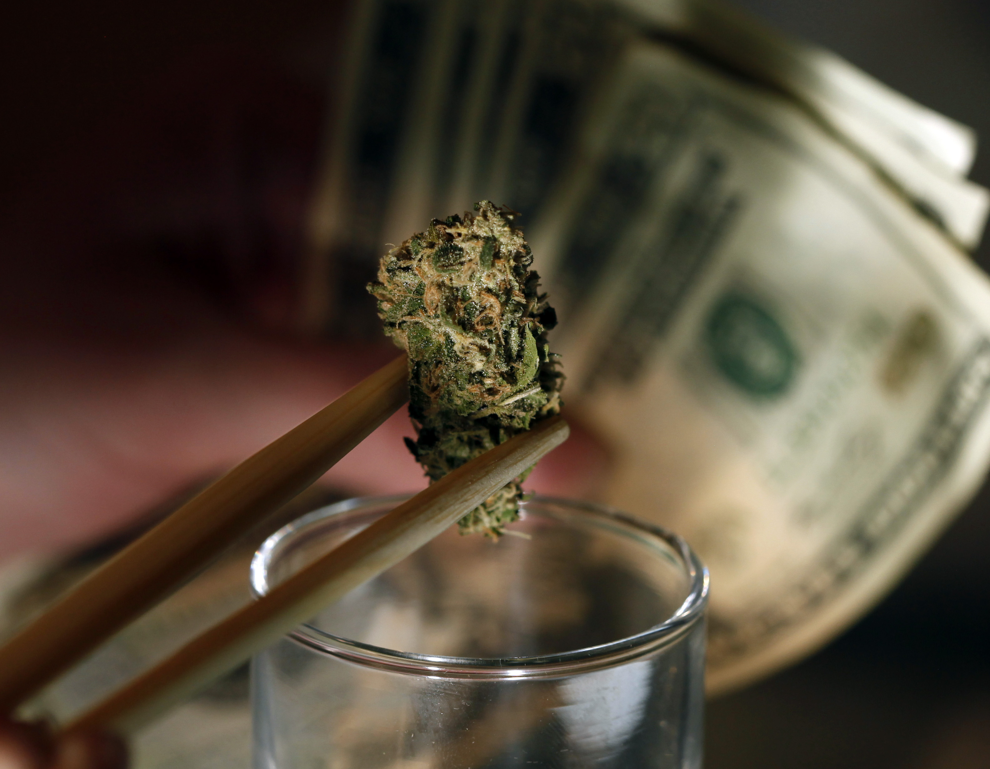 Photo: Marijuana bud, dollars bills in background, Denver dispensary (AP Photo)