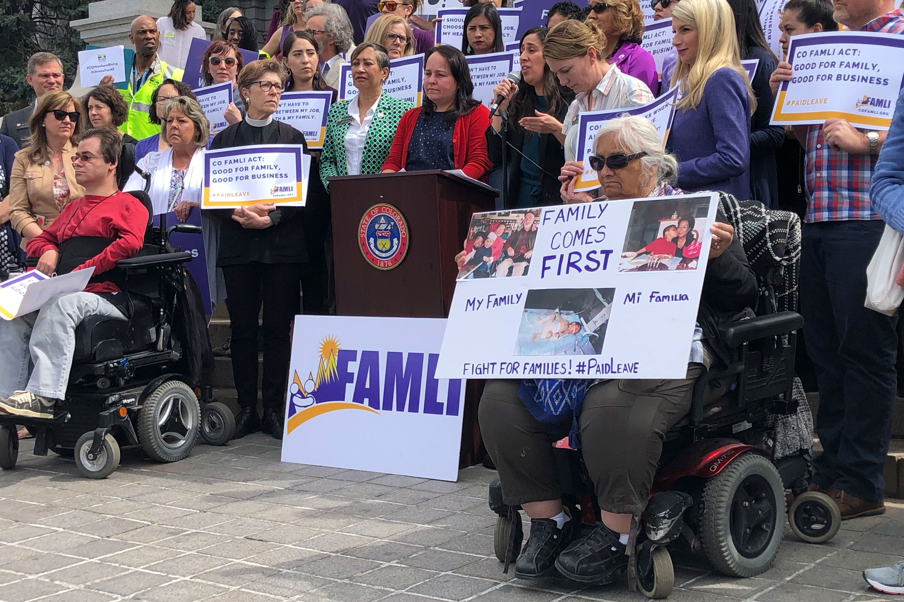 <p>Colorado Democratic Sens. Angela Williams and Faith Winter listen behind the podium as activist Judith Marquez speaks in favor of their paid family leave bill at a rally outside the statehouse on Tuesday, April 9, 2019, in Denver. </p>