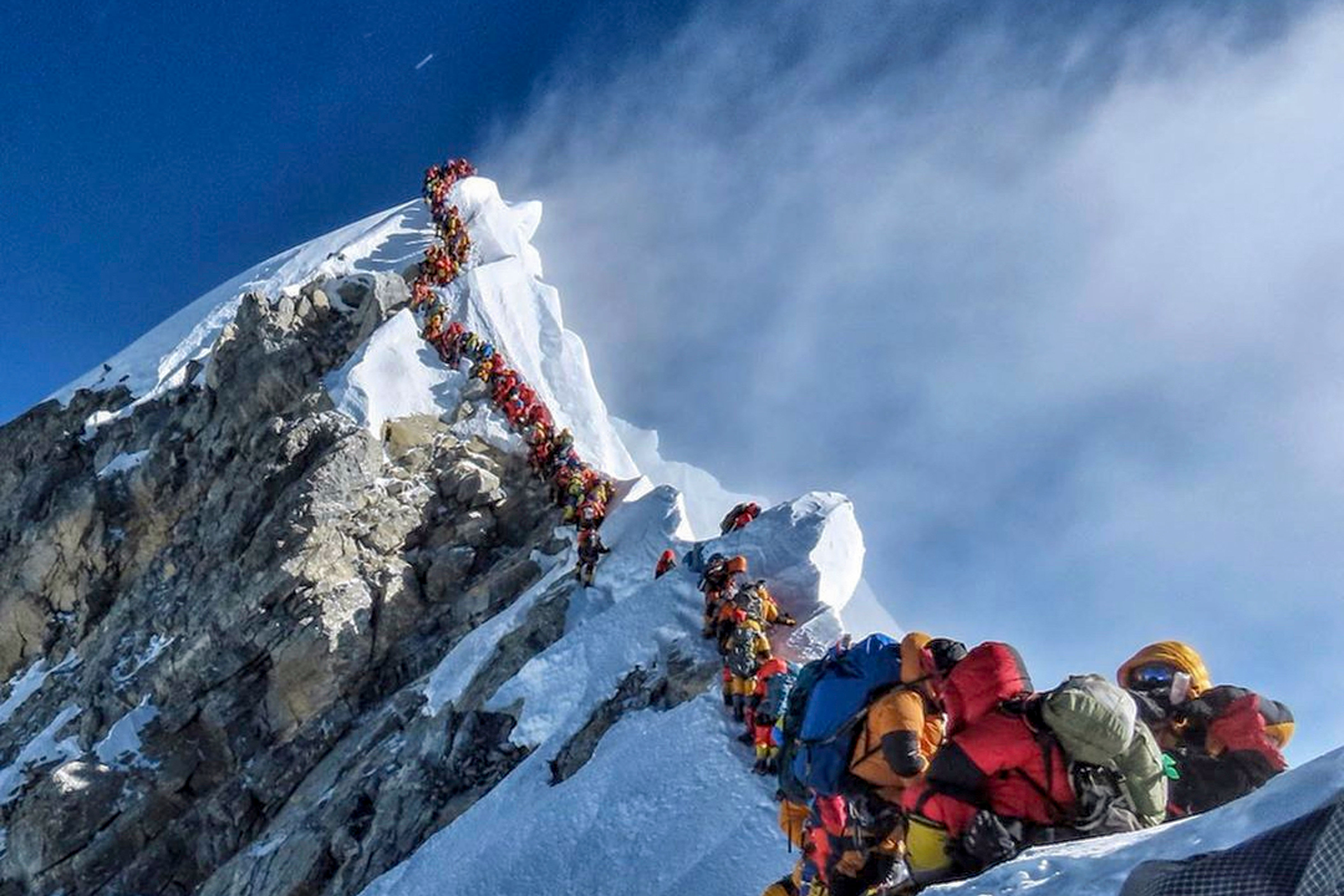 <p>In this photo made on May 22, 2019, a long queue of mountain climbers line a path on Mount Everest. About half a dozen climbers died on Everest last week most while descending from the congested summit during only a few windows of good weather each May.</p>