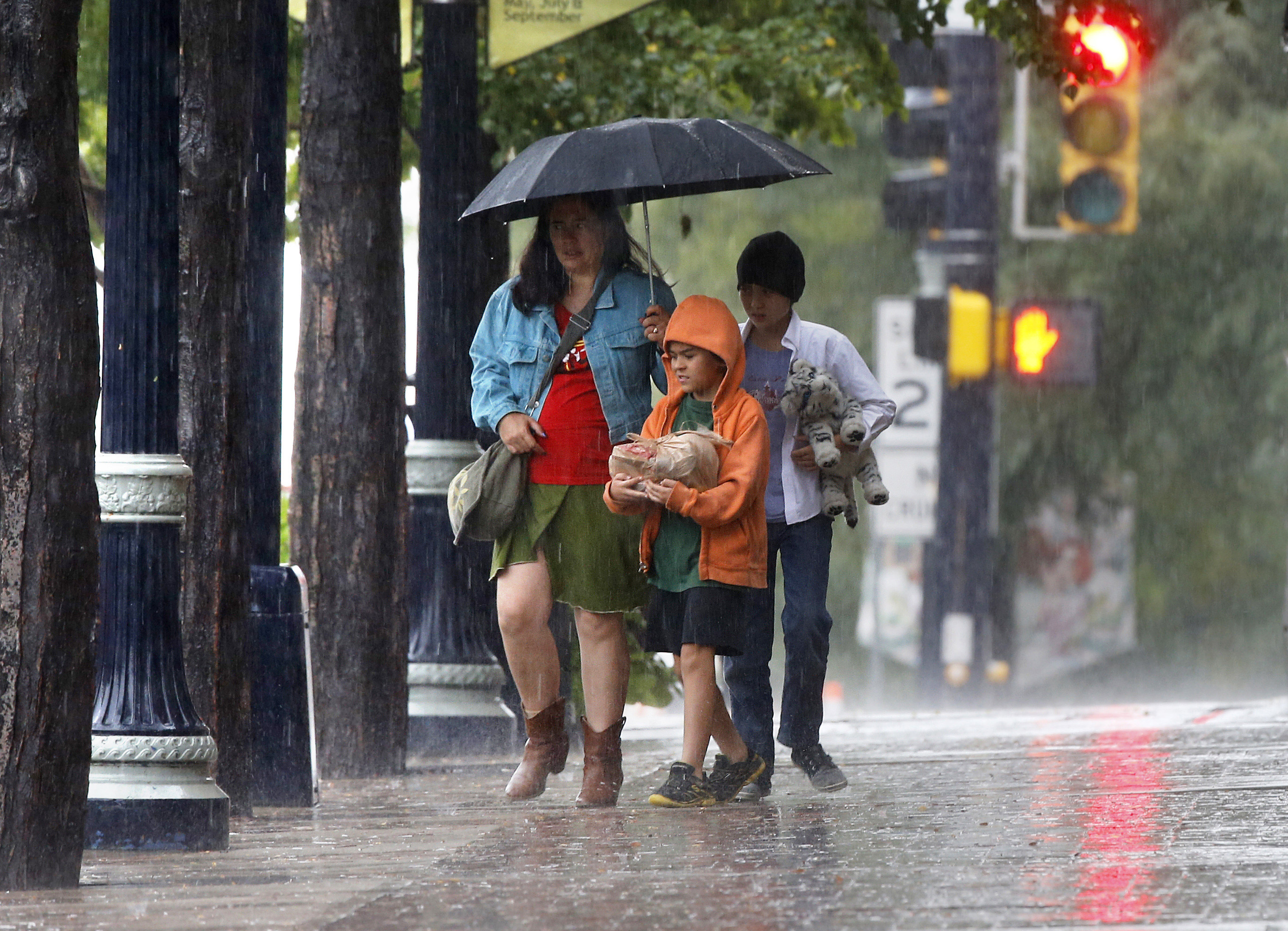 Photo: Walking in rain in September 2013 (AP Photo)