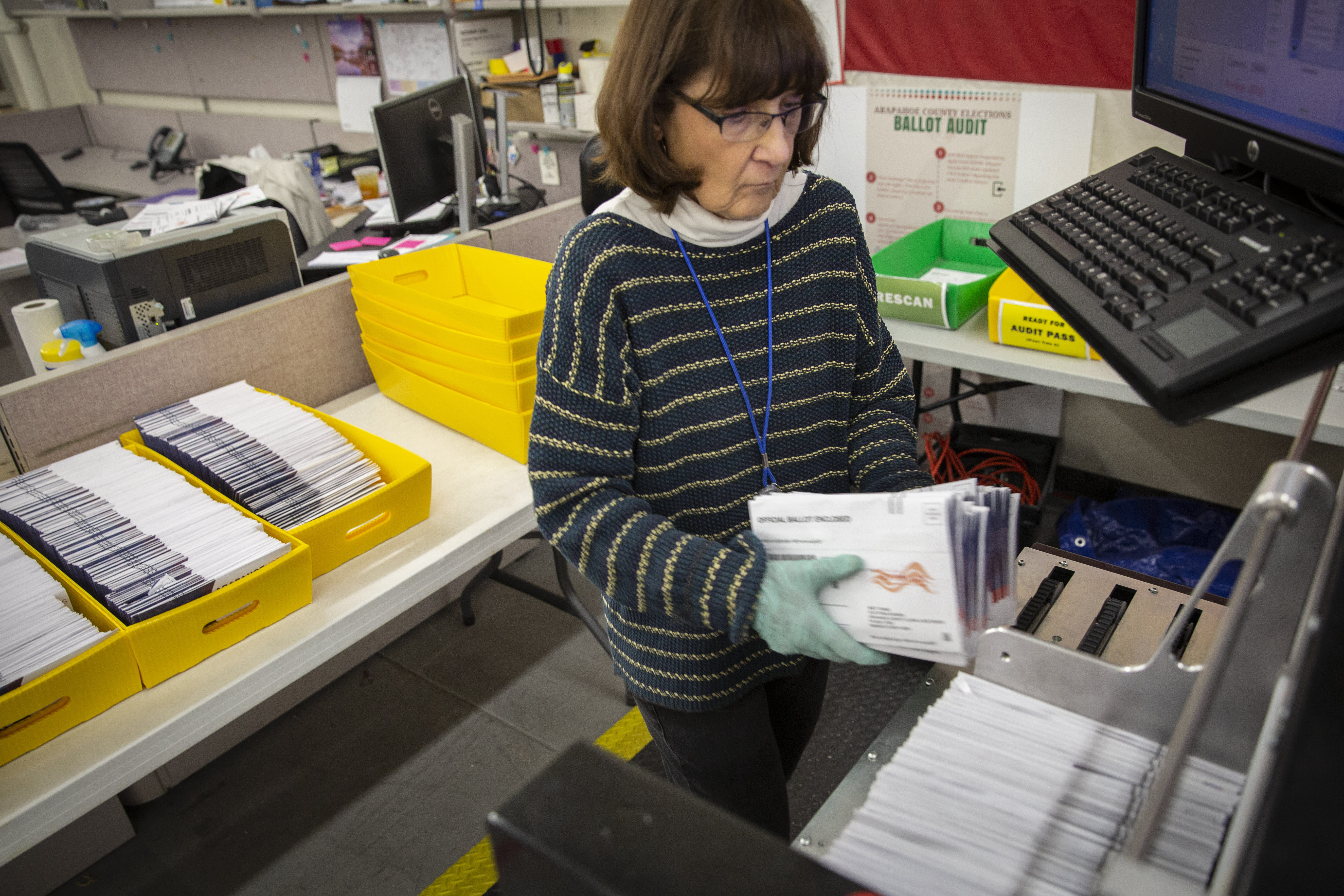Marleen Cohen of Aurora loads ballots into a sorting machine at the Arapahoe County Elections Facility in Littleton, Colorado, Tuesday, Oct. 30, 2018.