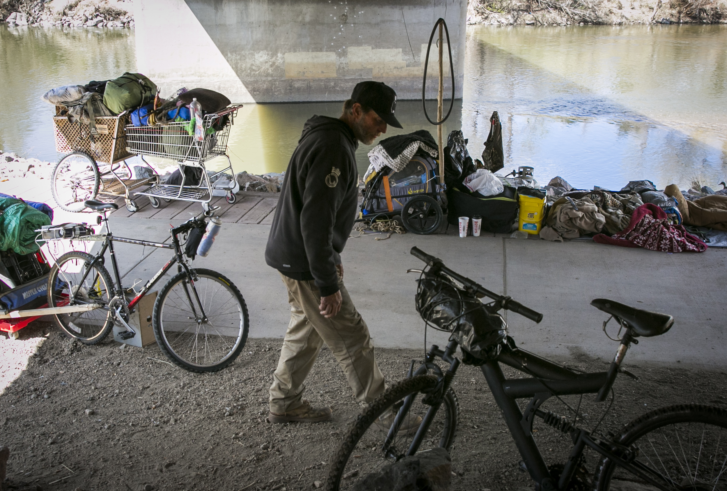 Robin Kendrick, who's homeless, stands amid shopping carts. bicycles and other homeless people's possessions near the South Platte River on Friday, April 1, 2016.
