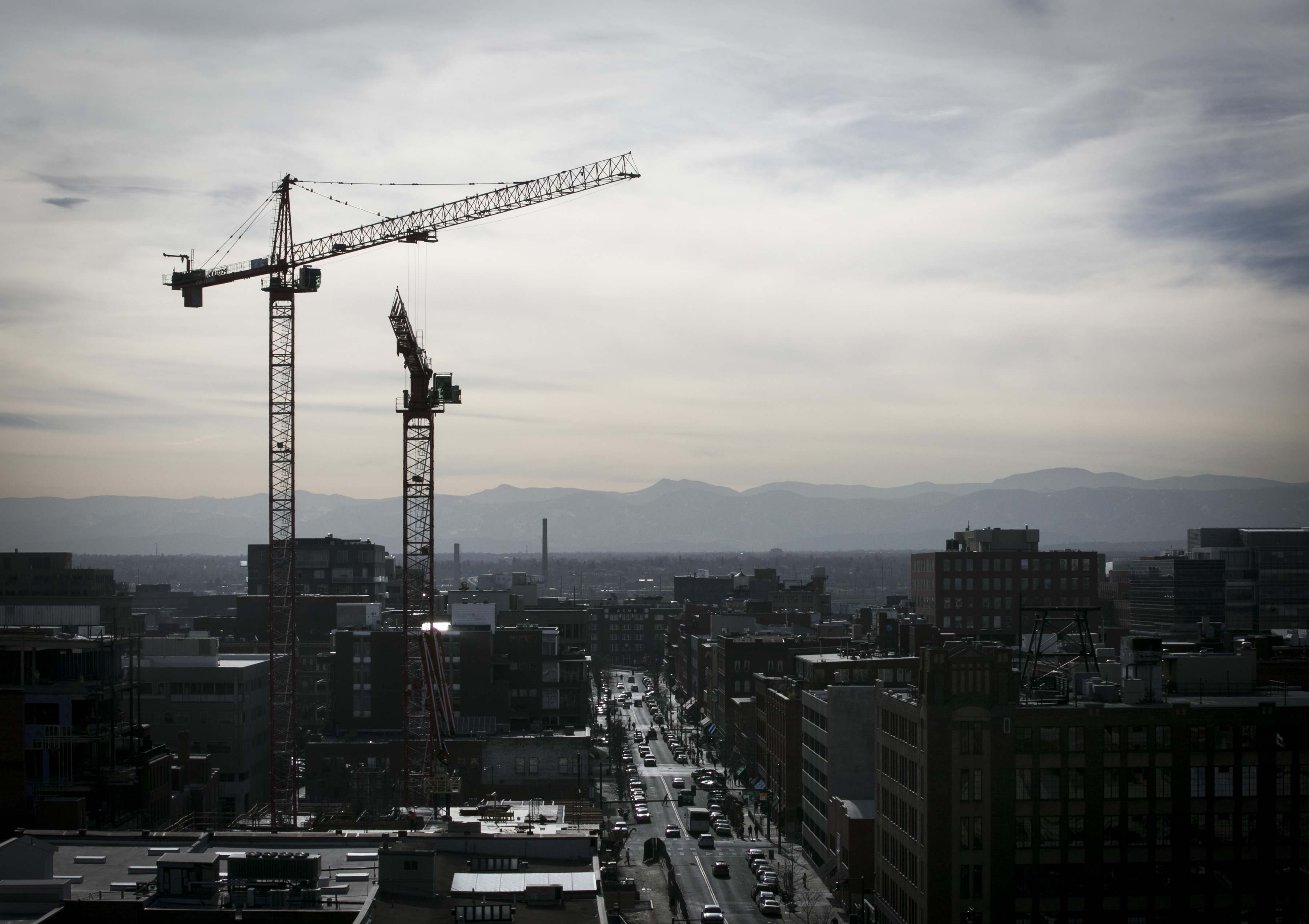 Construction cranes stand over lower downtown Denver on Thursday, Feb. 18, 2016.