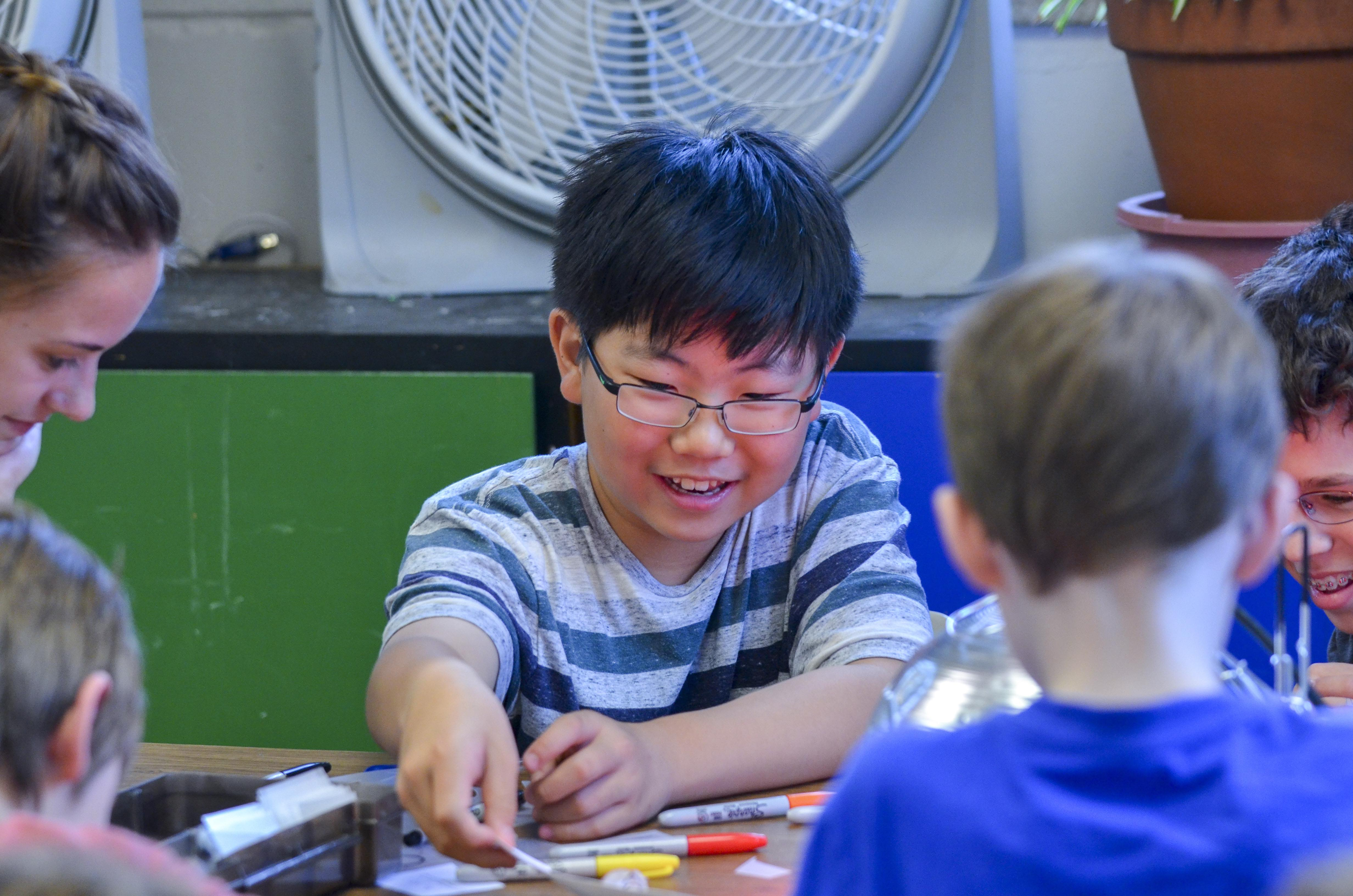 Eliot Hwang, 11, experiments with making bending polymers under a heat lamp at the CU Science Discovery summer camp.