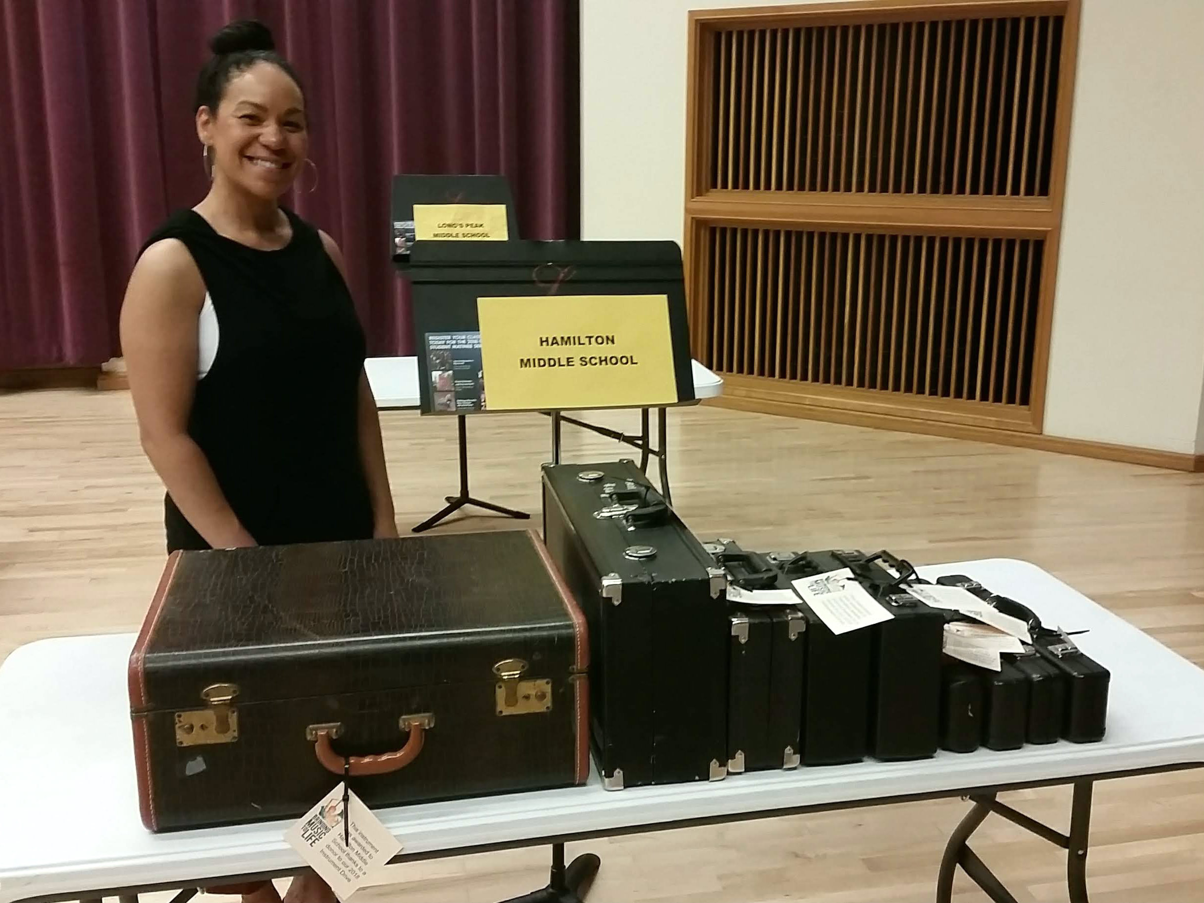 <p>Hamilton Middle School band teacher Priscilla Shaw poses with instruments she's picking up from the Bringing Music to Life instrument distribution day. </p>