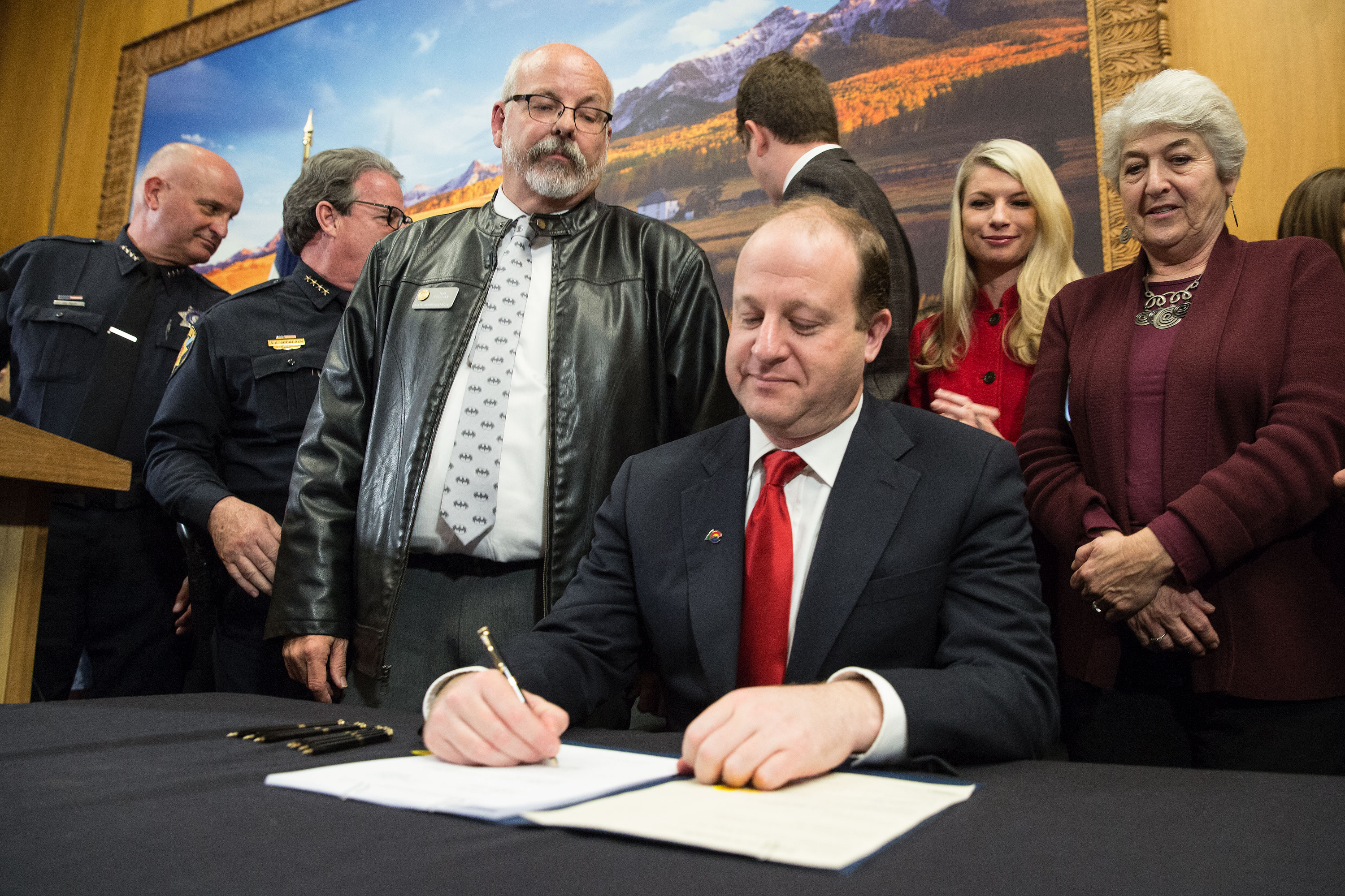 State Rep. Tom Sullivan watches as Gov. Jared Polis signs HB 1177, the Red Flag bill, into law on April 12, 2019. Sullivan, a freshman lawmaker, campaigned for office in part to enact tougher gun control laws after his son Alex was murdered in the Aurora theater shooting. He was a leading sponsor of the bill.