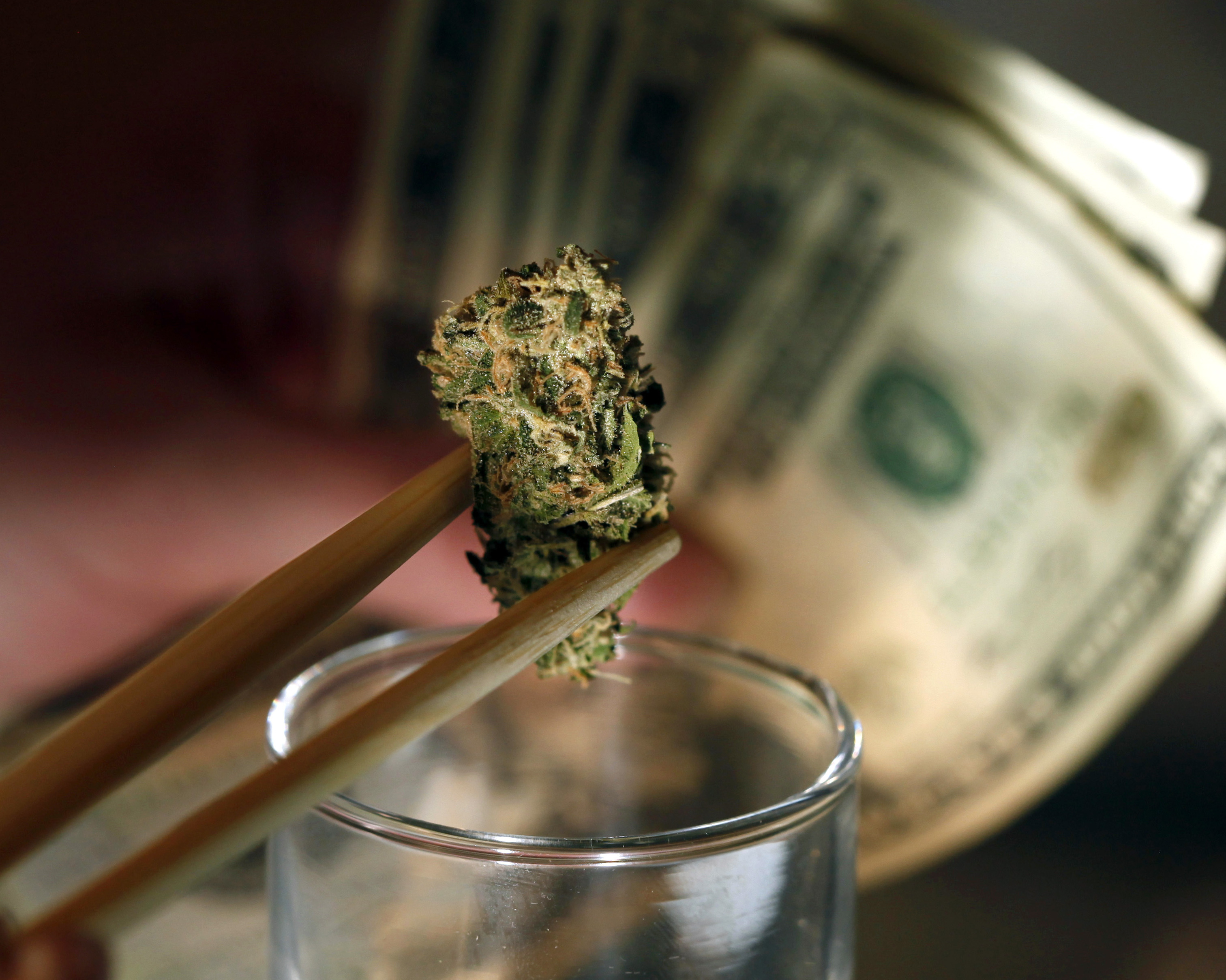 A marijuana bud and cash at a shop in Denver. An owner of marijuana stores in the city says of his company's bank account,
