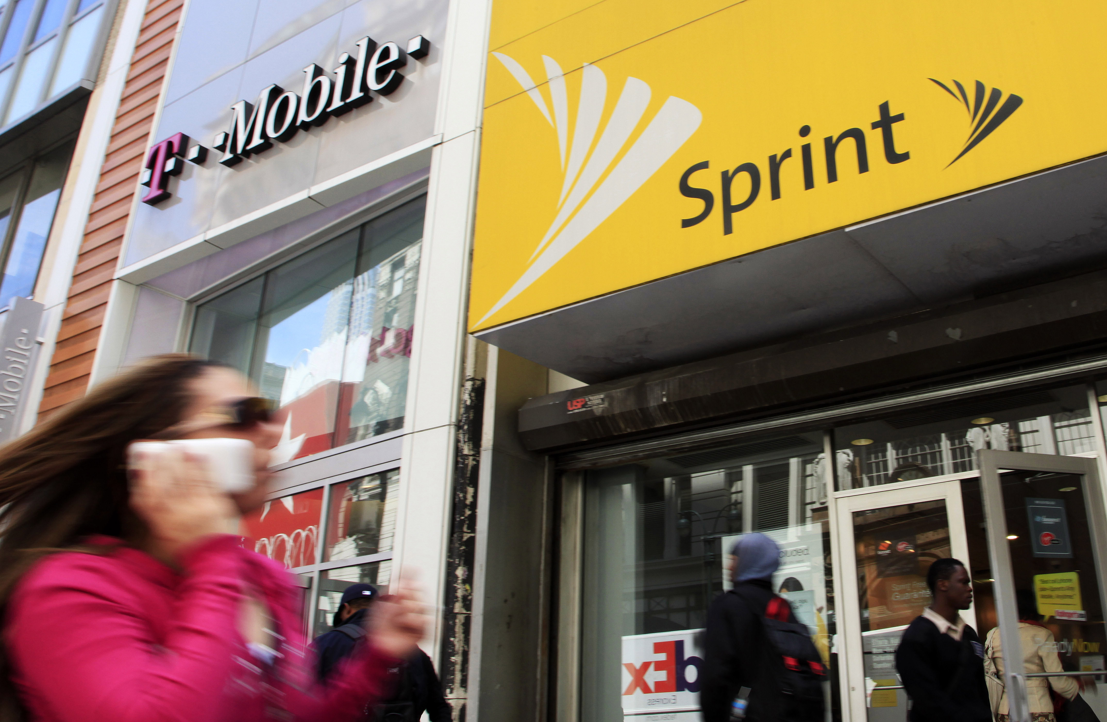 A woman using a cell phone walks past T-Mobile and Sprint stores in New York.