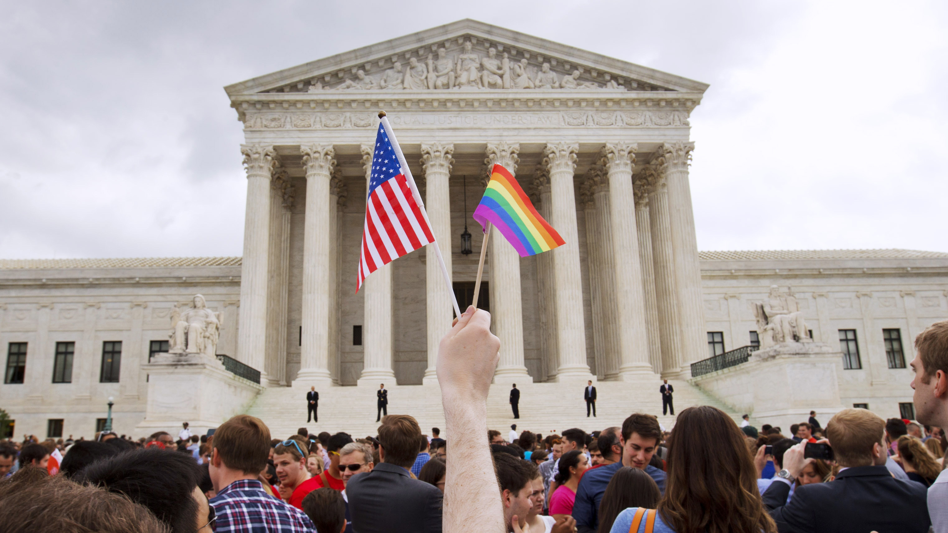 A man holds a U.S. and a rainbow flag outside the Supreme Court in Washington after the court legalized gay marriage nationwide, June 26, 2015.
