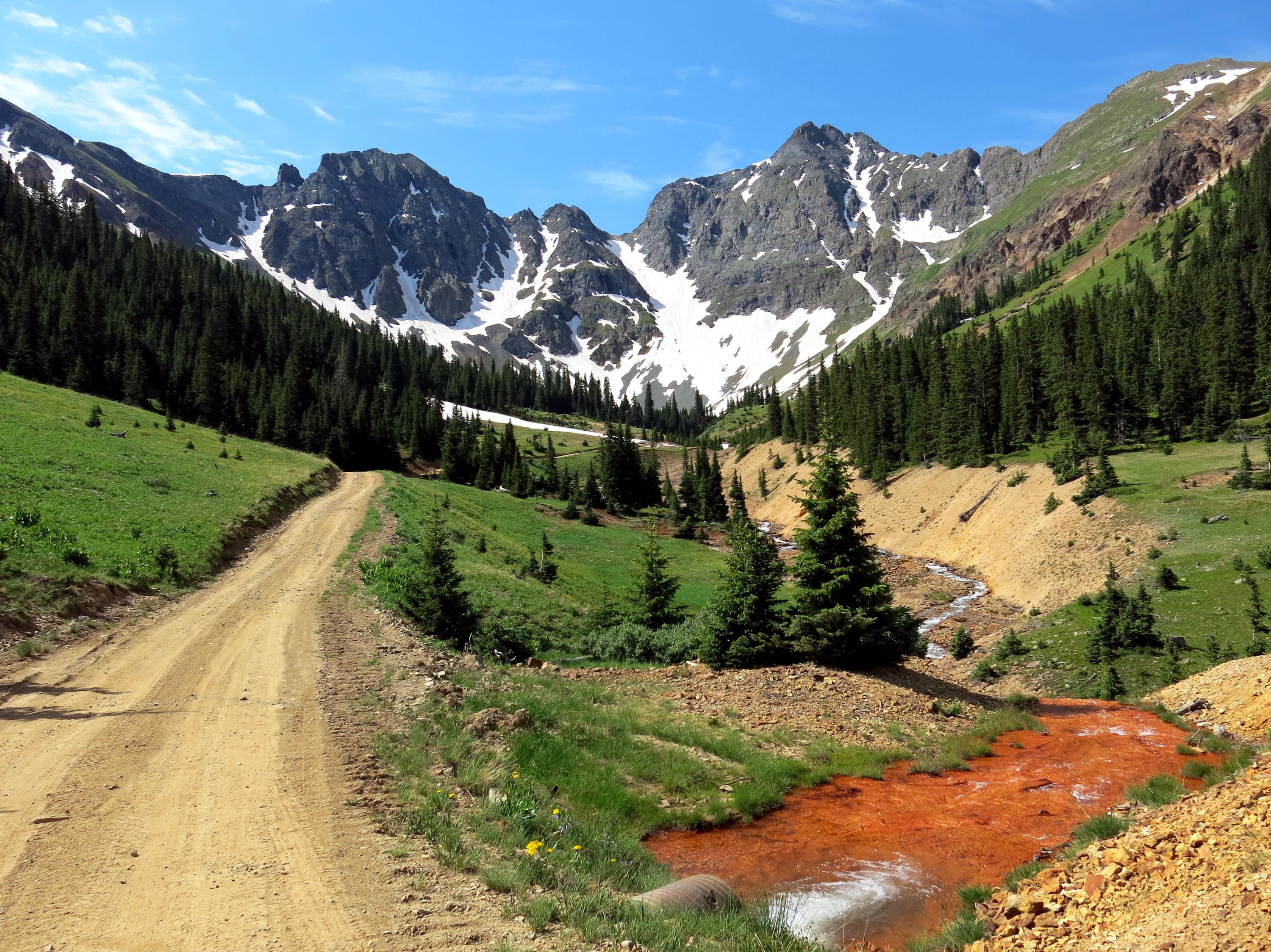 Orange sediment laced with heavy metals is visible in the path of water coming out of the Natalie/Occidental Mine in southwestern Colorado. This mine is one of dozens on a proposed Superfund listing pending with the EPA. Several mines in the area have been leaching the tainted water for years — well before the Gold King Mine spill.