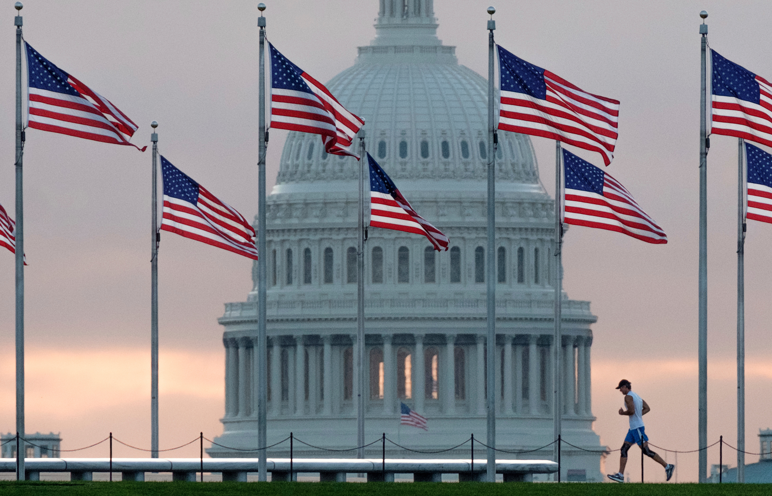 An early morning runner crosses in front of the U.S. Capitol as he runs around the Washington Monument in D.C. Control of Congress and power in Washington is at stake this Fall.