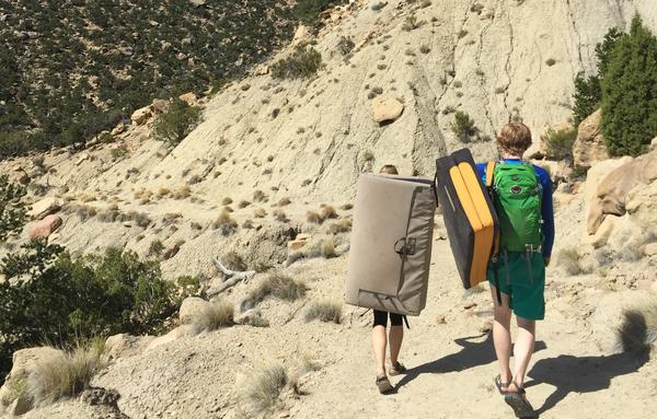 Joe's Valley, Utah is an internationally popular destination for rock climbers. Here, climbers carrying crash pads used for bouldering head out on the trail.