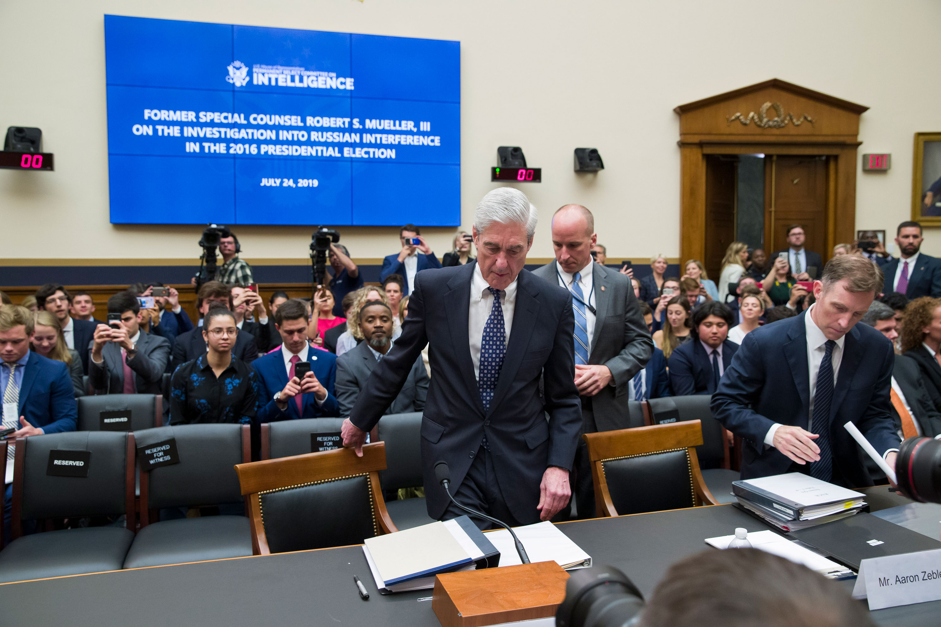 Former special counsel Robert Mueller, accompanied by his top aide in the investigation Aaron Zebley, takes his seat to testify before the House Intelligence Committee hearing on his report on Russian election interference, on Capitol Hill, Wednesday, July 24, 2019 in Washington.