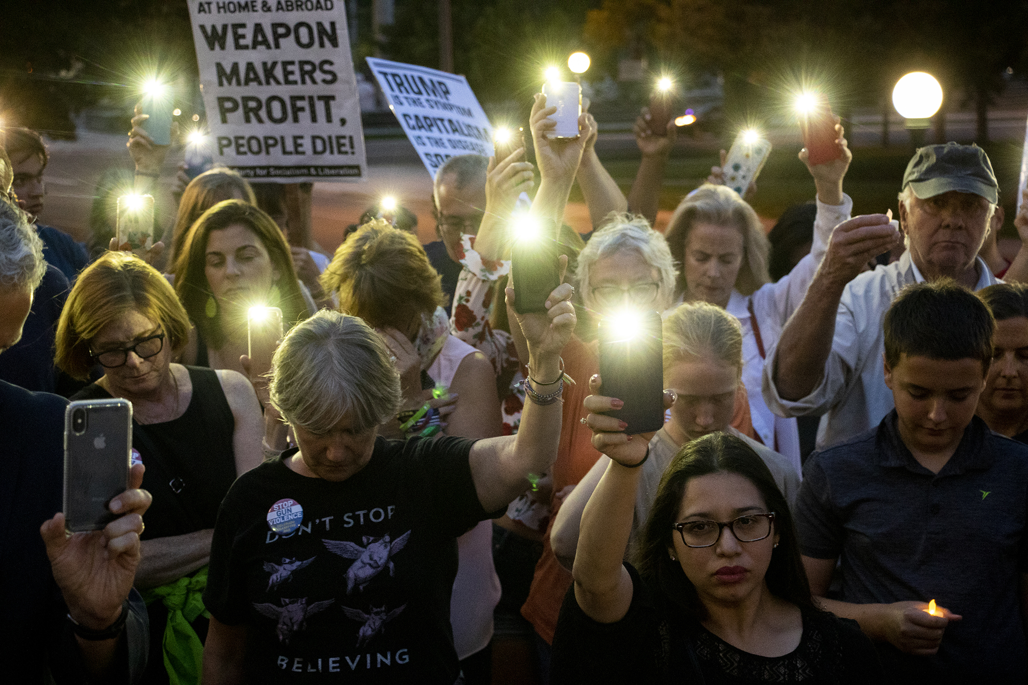 People hold up camera lights as candles during a vigil for victims of gun violence on the Capitol steps, Aug. 4, 2019.