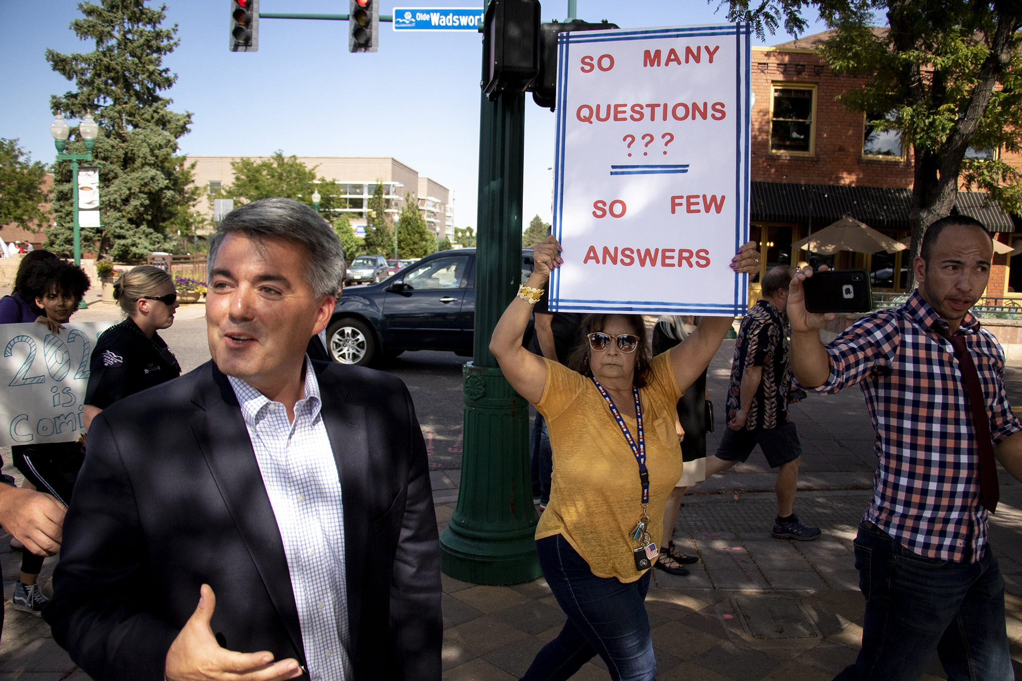 Susan Glass, chair of the Jefferson County Democratic party, holds a protest sign as Sen. Cory Gardner visits Arvada businesses, Aug. 13, 2019.