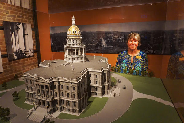 Colorado state Capitol tour guide Ellen Stanton poses next to a model of the building. Before she moved to Colorado, Stanton served as a tour guide at Mount Vernon and the U.S. Capitol.