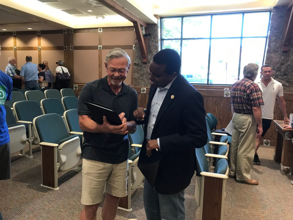 Rep. Joe Neguse speaking with Estes Park resident Richard Mulhern at the end of a town hall.