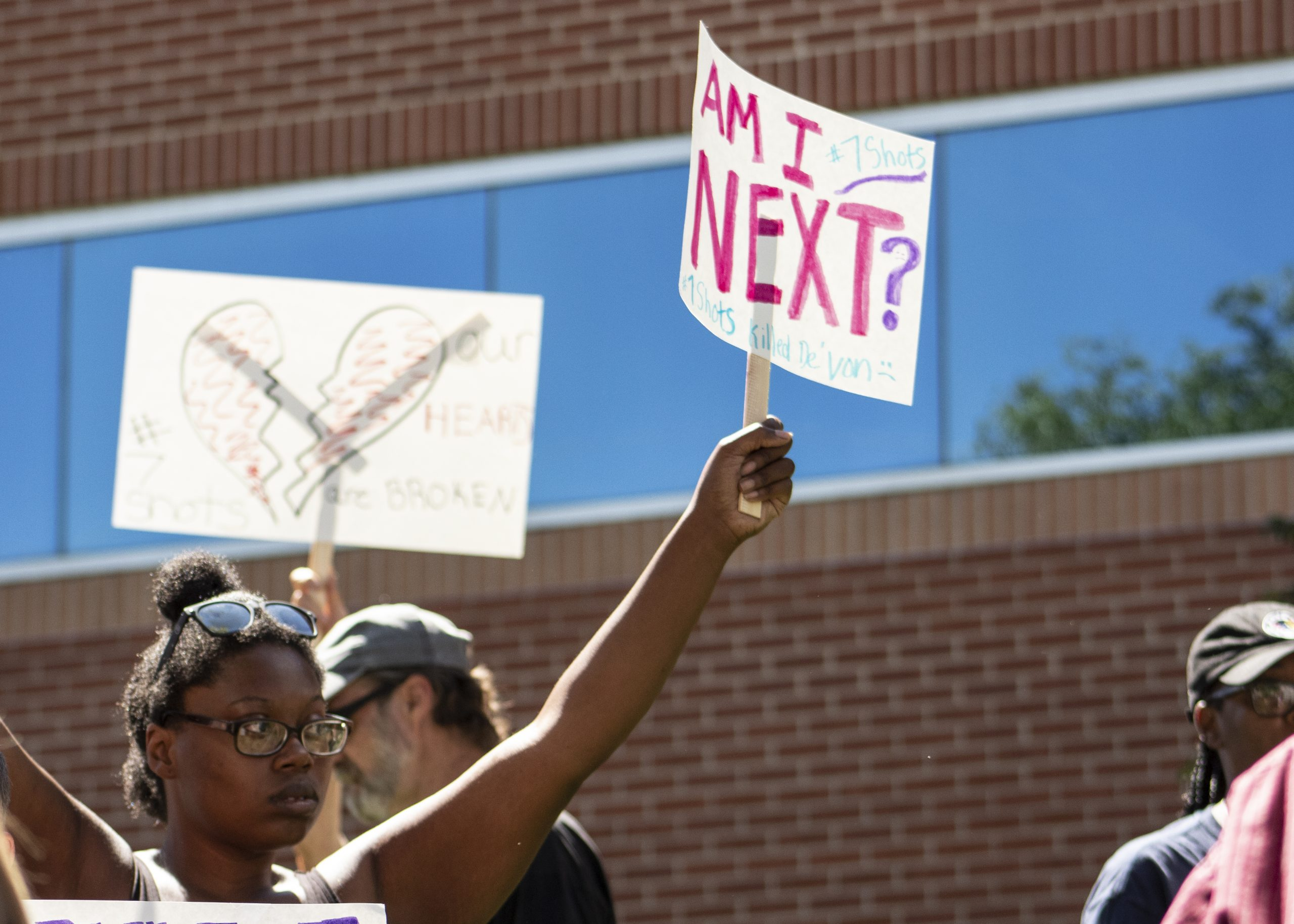 """A young woman raises a sign that reads """"Am I Next?"""""""
