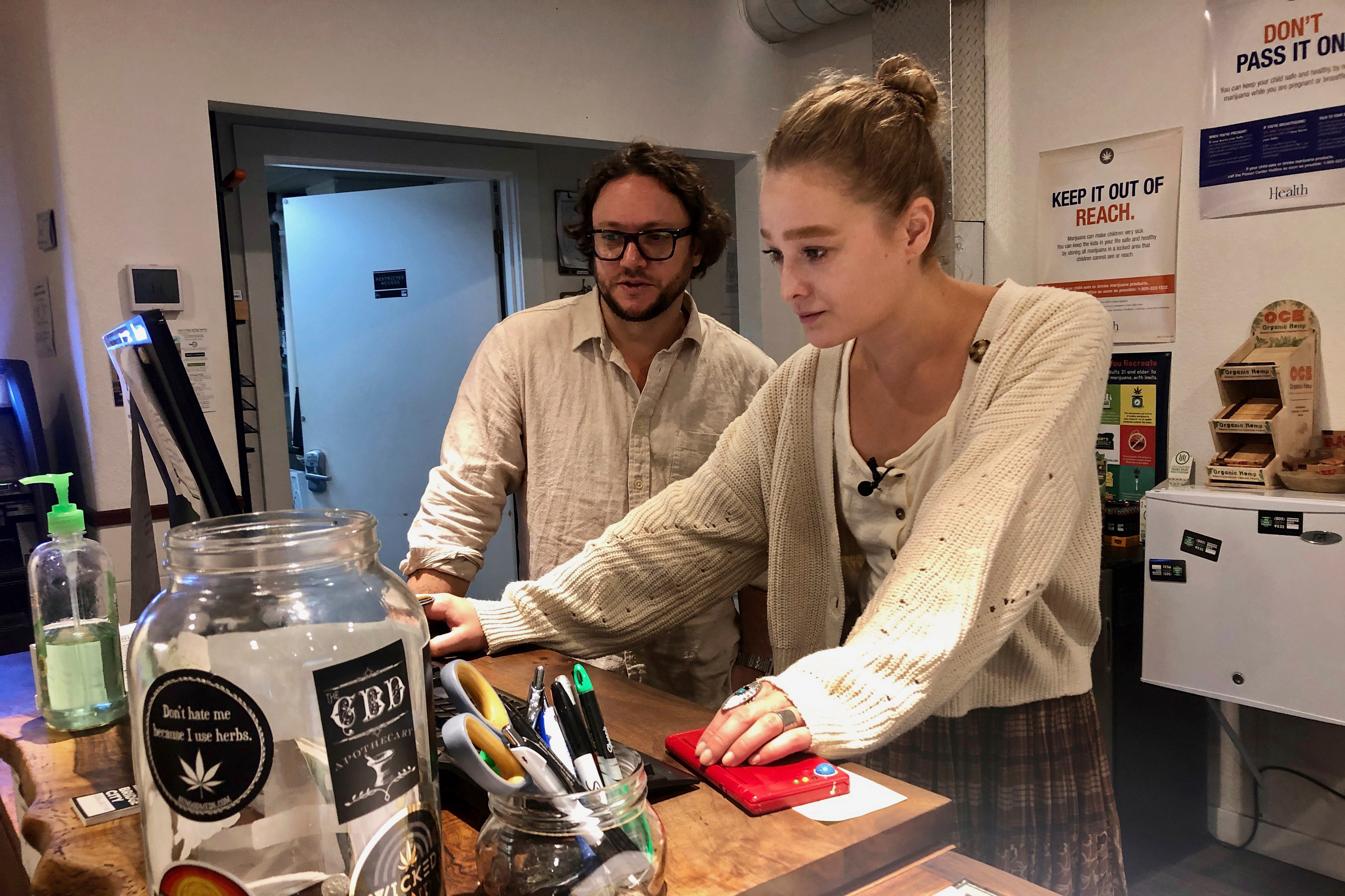 """In this photo taken Sept. 20, 2019, David Alport, owner of the Bridge City Collective marijuana dispensary in Portland, Ore., goes over sales numbers with the store's general manager Cameron Moore. The company has seen a 31 percent decrease in its sales of vaping products in the past two weeks. """"It's having an impact on how consumers are behaving,"""" said Alport. """"People are concerned, and we're concerned."""""""