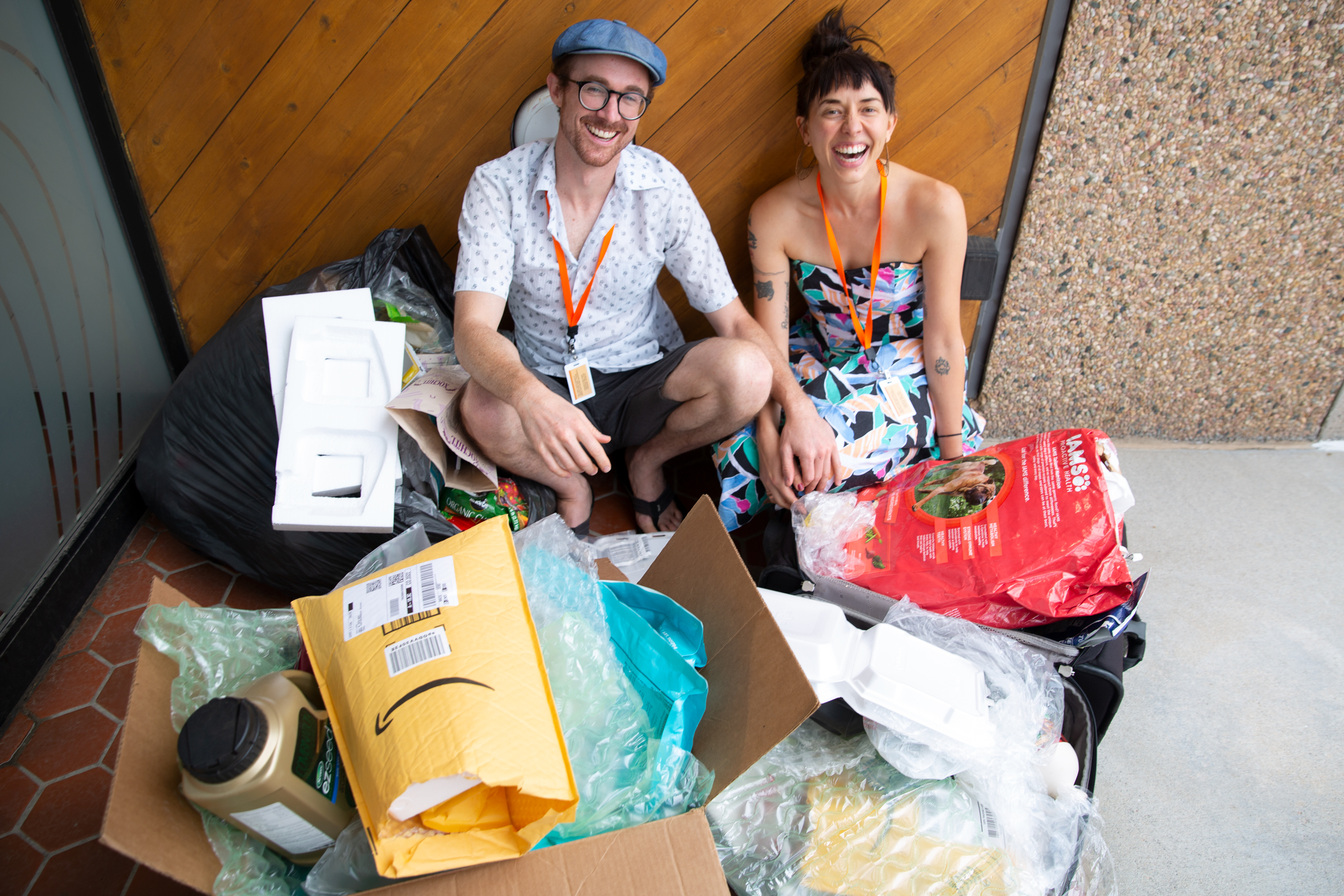 """Kevin Larkin and Erica Prather sit amongst all the plastic they've used so far in 2019. It's contained in one suitcase, a large box and a large trash bag — their """"Pile of Petroleum Past."""""""