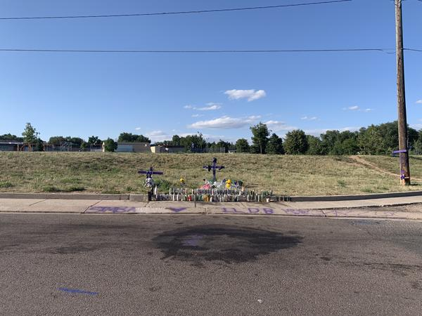People have left flowers and candles near the stained asphalt, marking the spot where Bailey was shot.