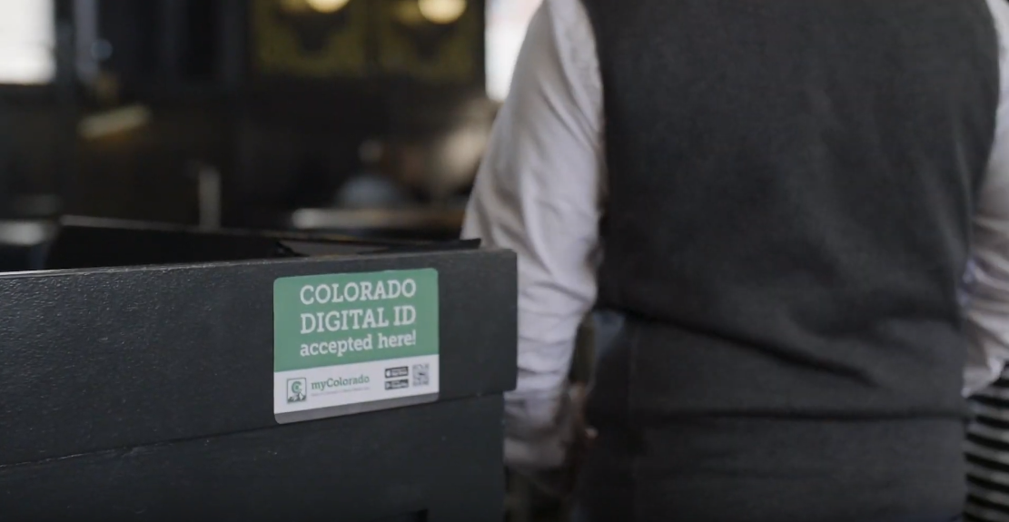 A screencap from  a promotional video showing a bar outfitted with a myColorado digital ID sticker.