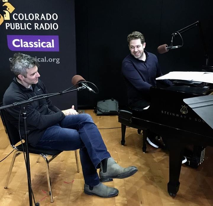Kevin Puts sits in front of a microphone while Brett Mitchell sits at the piano in the CPR Performance Studio