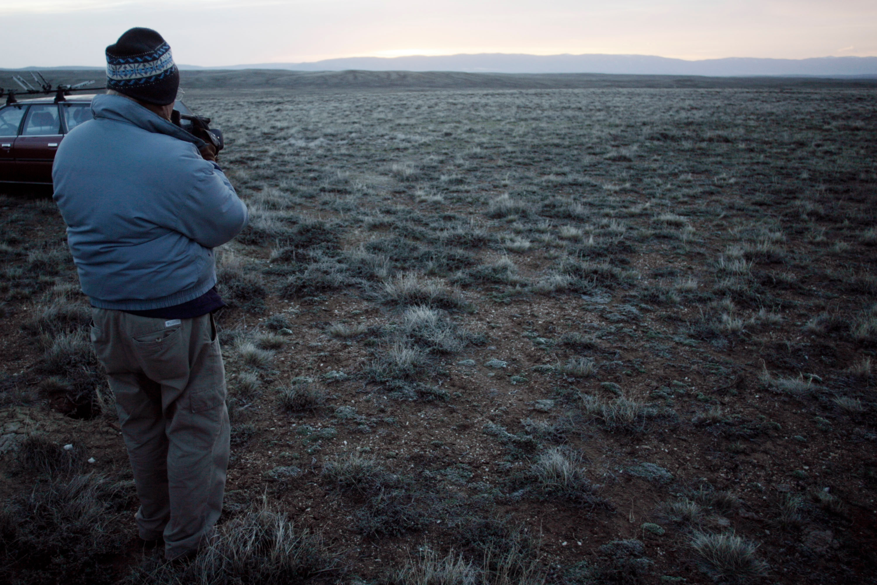 An unidentified bird watcher emerges from a blind to watch the sun rise over the sagebrush where the greater sage grouse perform their annual mating ritual near the North Park community of Walden, Colo., April 21, 2007.