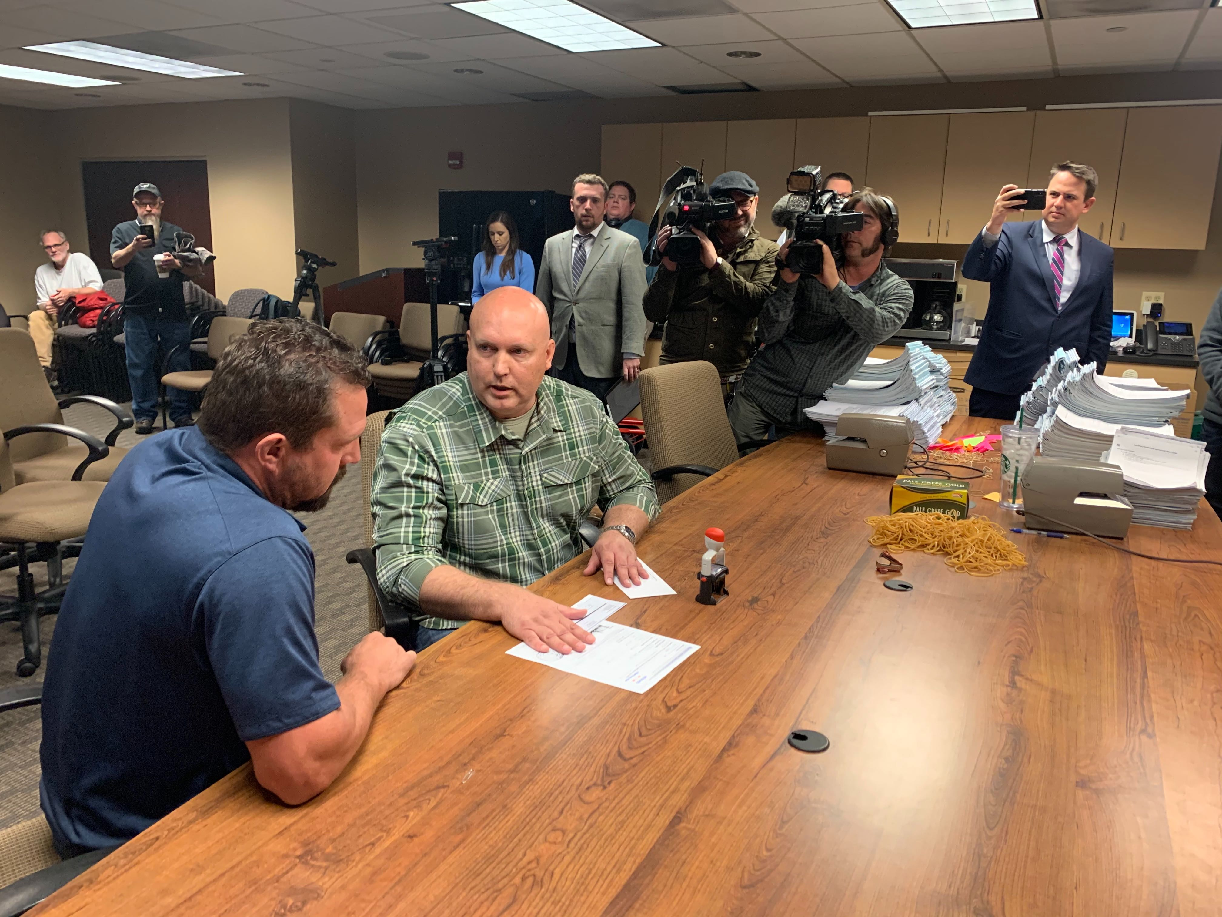 """John """"Tig"""" Tiegen, representing President Donald Trump's re-election campaign, files paper work with Joel Albin, ballot access manager for the Colorado Secretary of State's Office on Tuesday, Nov. 12, 2019."""