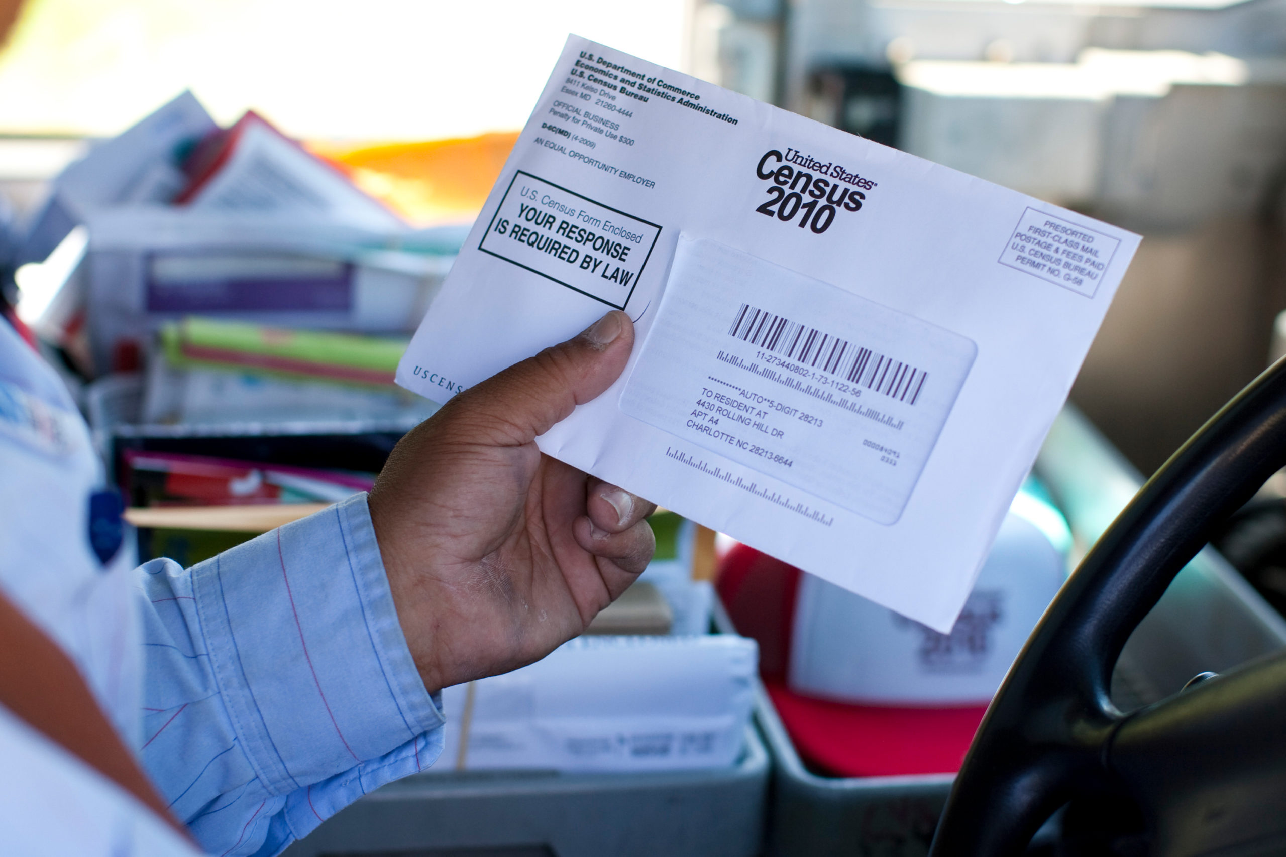 US Postal Service mail carrier Thomas Russell holds a 2010 Census form while working his route.