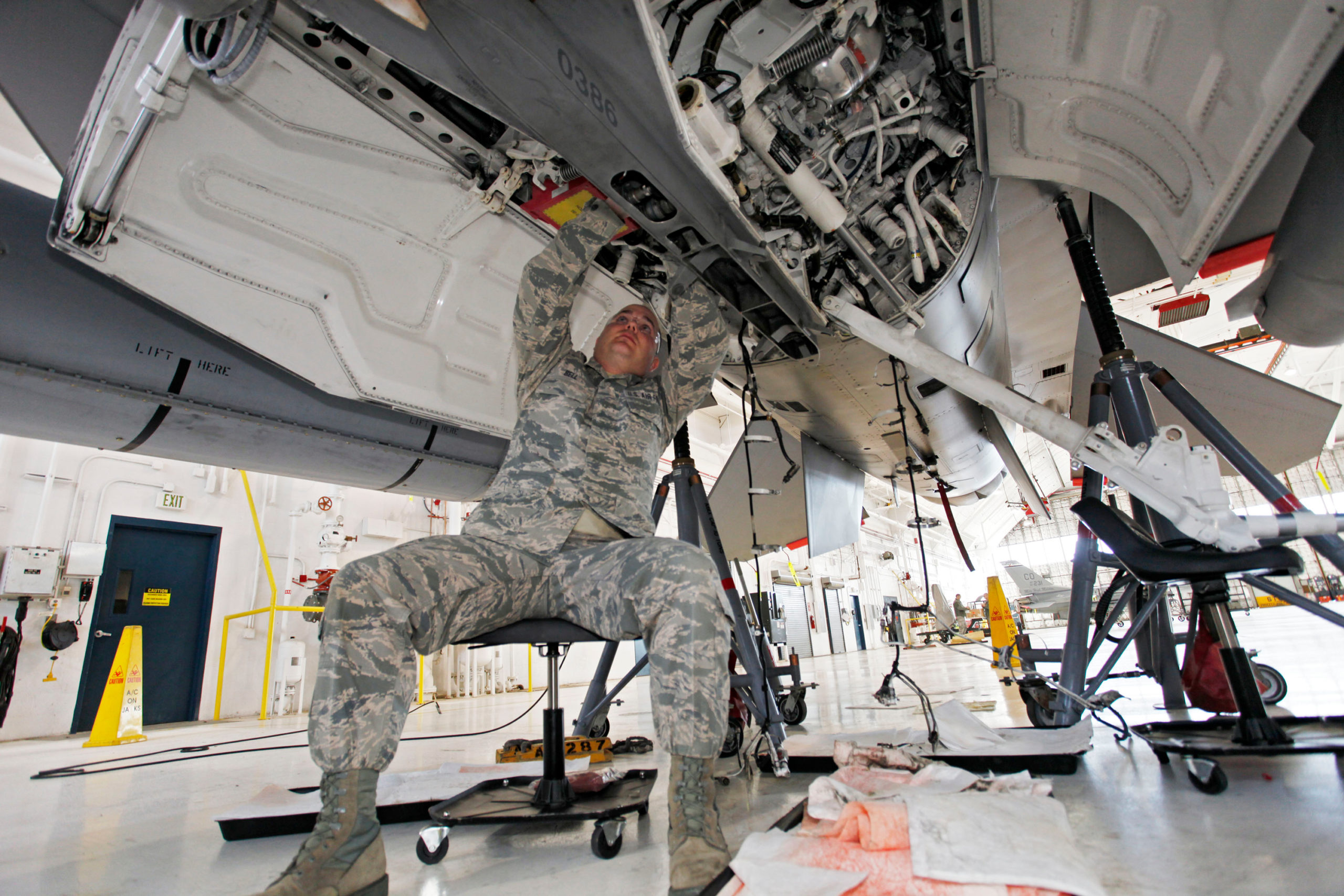 Master Sgt. Kenneth Bell, a metal technology specialist, checking the hydraulic system on an F-16 undergoing a routine checkup in a hangar at Buckley Air Force Base east of Denver. The F-16s, based at Buckley, are flown by a Colorado Air National Guard unit and have often been called on by NORAD to track down and escort planes that violate restricted airspace or otherwise arouse suspicion.