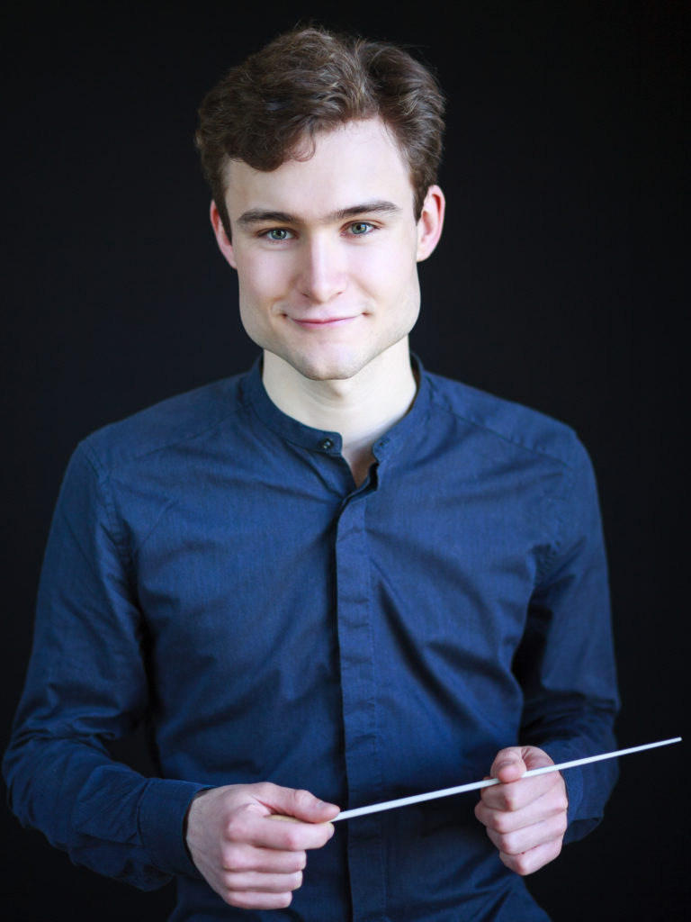 Assistant Conductor Bertie Baigent wearing a blue shirt, holding a batton, with a closed mouth smile.