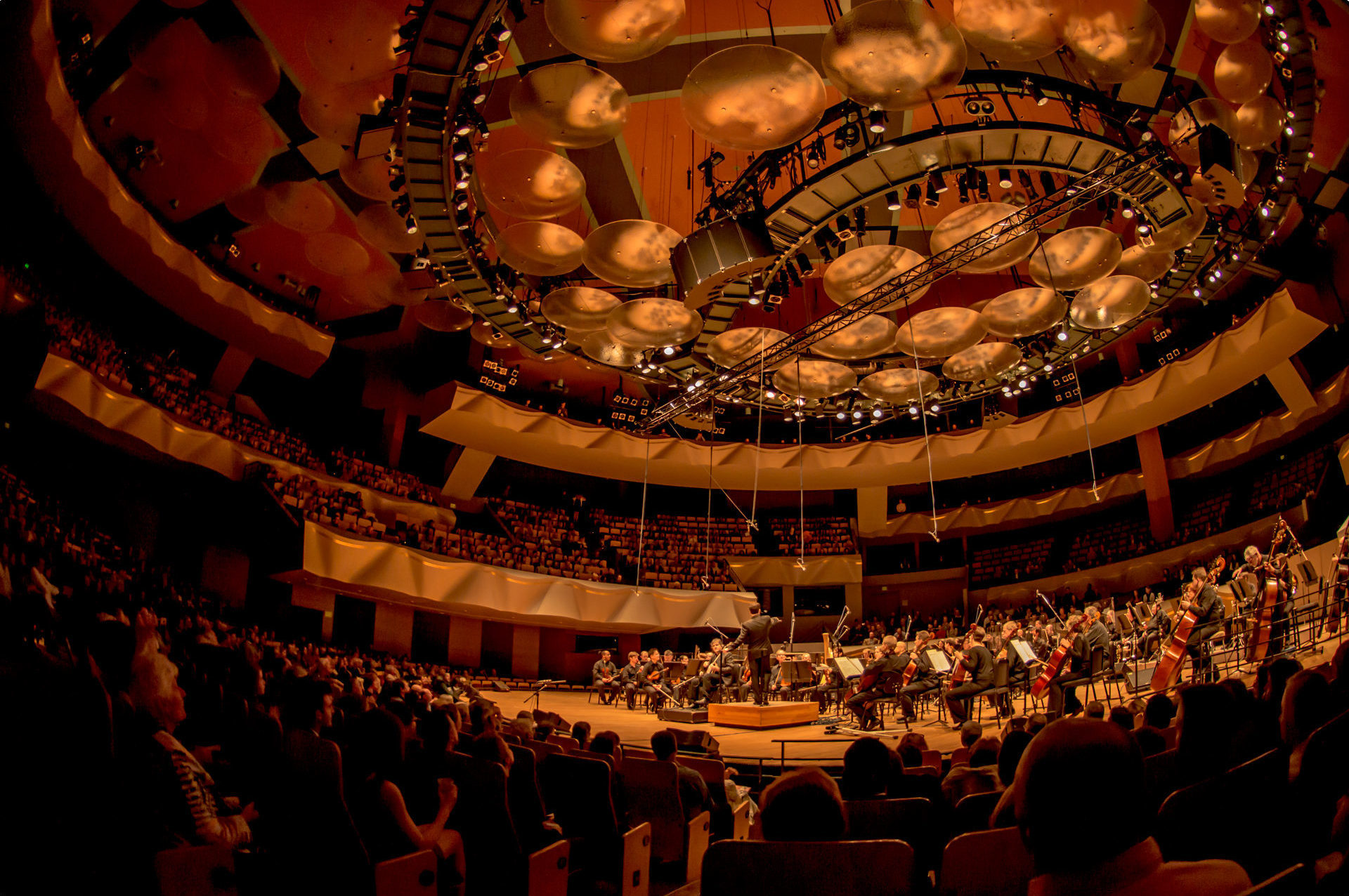 Boettcher Concert Hall lights dimmed, with full audience and symphony on stage