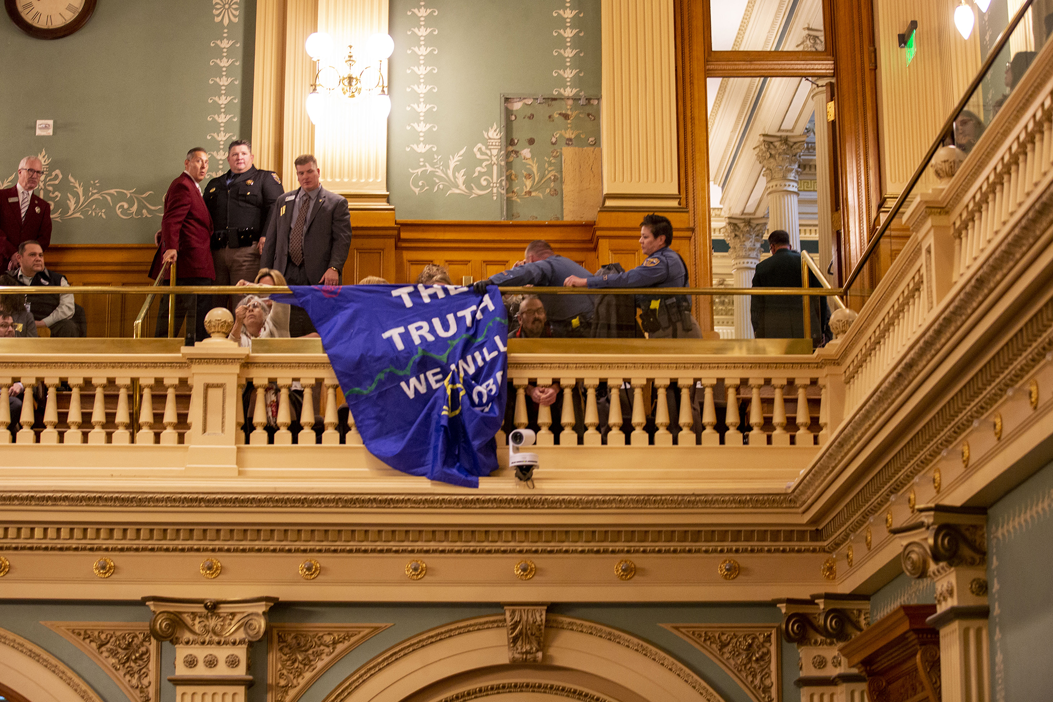 Environmental activists drop a banner from the House gallery before Gov. Jared Polis' State of the State address, Jan. 9, 2020.