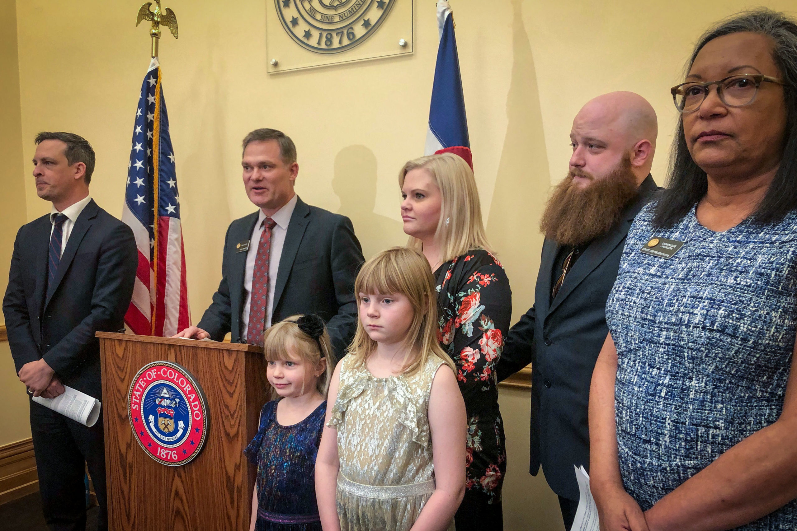 Democratic Senate Majority Leader Steve Fenberg and Sen. Mike Foote stand alongside a Colorado family who described a difficult arbitration issue they lived through at a news conference at the capitol, Jan. 15, 2020. Democratic Rep. Dominque Jackson, far right, supports new legislative changes to arbitration in Colorado.