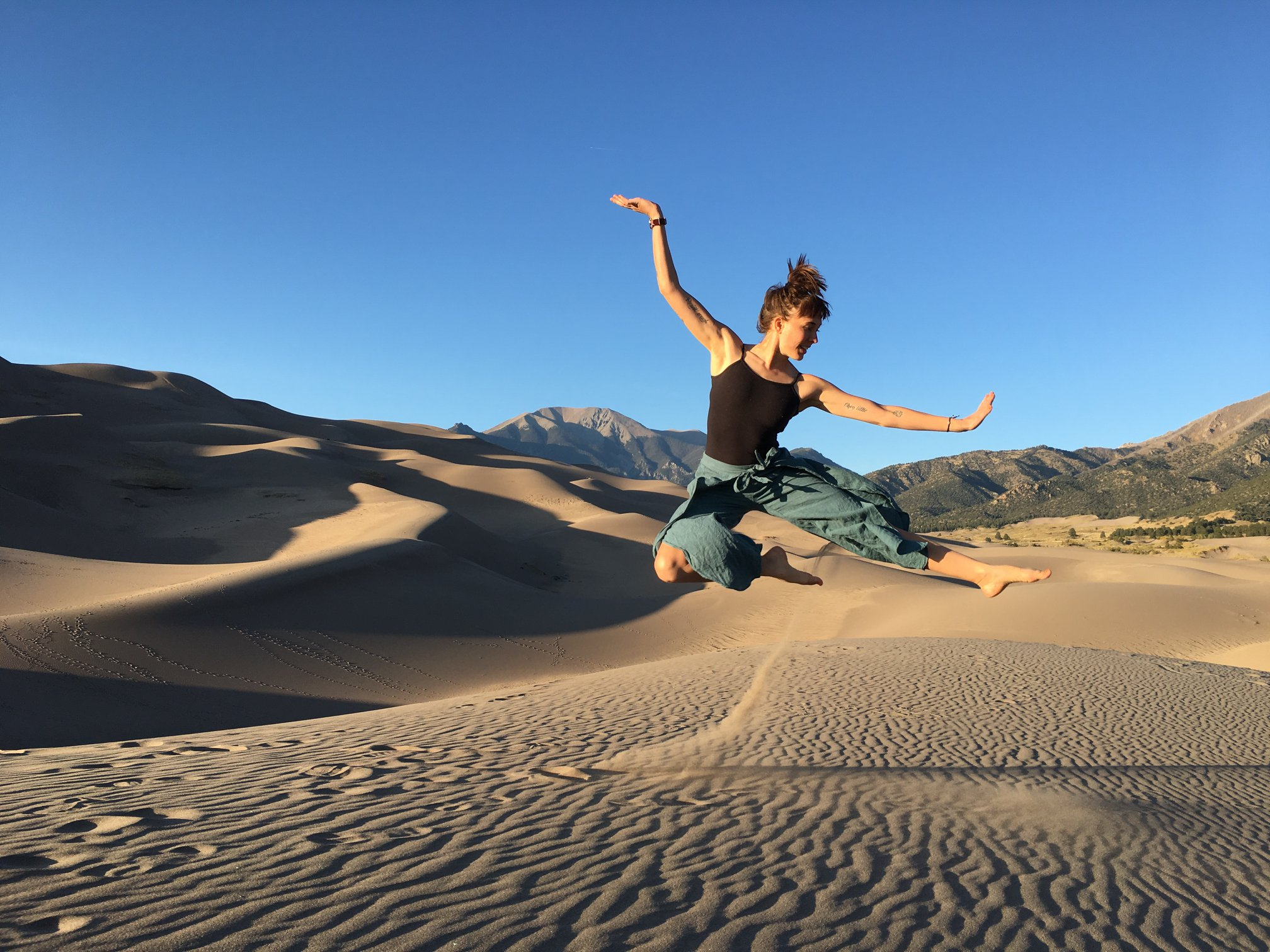 Erica Prather performing at the Great Sand Dunes National Park during her 2019 artist residency.