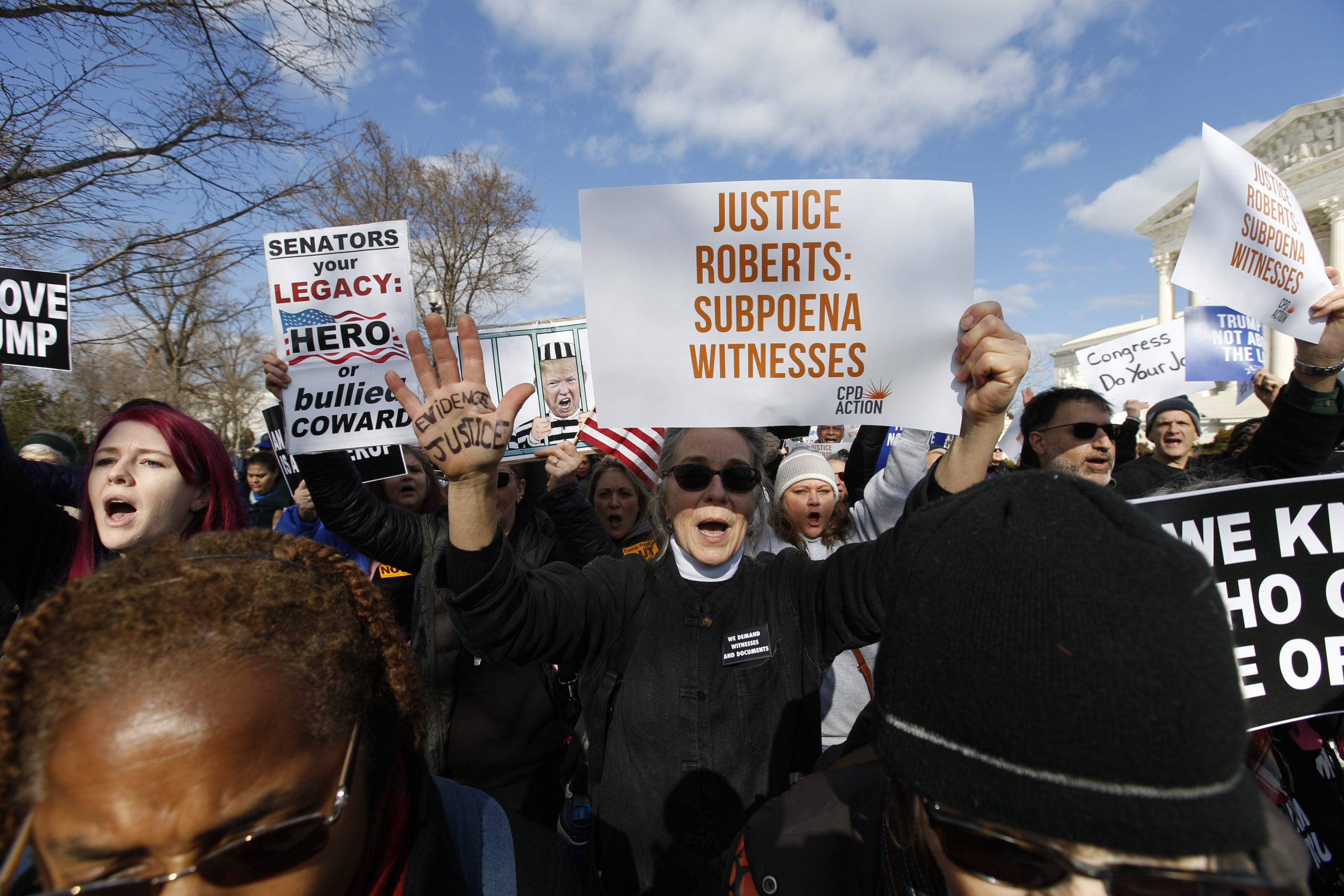 Demonstrators protest outside of the U.S. Supreme Court in Washington, Wednesday, Jan. 29, 2020, during the impeachment trial of President Donald Trump on charges of abuse of power and obstruction of Congress.