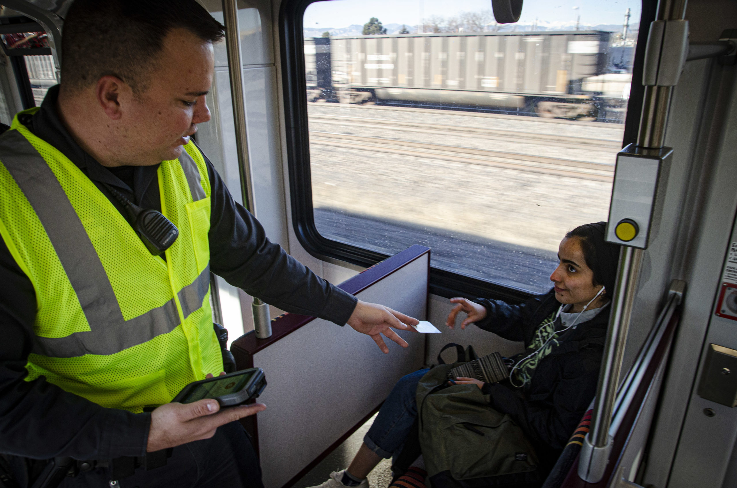 Jesse Balderrama, a security officer with Allied Security, an RTD contractor, hands a fare card back to passenger Afaf Al-Johani, a student at the University of Denver, on an RTD light rail train Wednesday, Jan. 15, 2019.