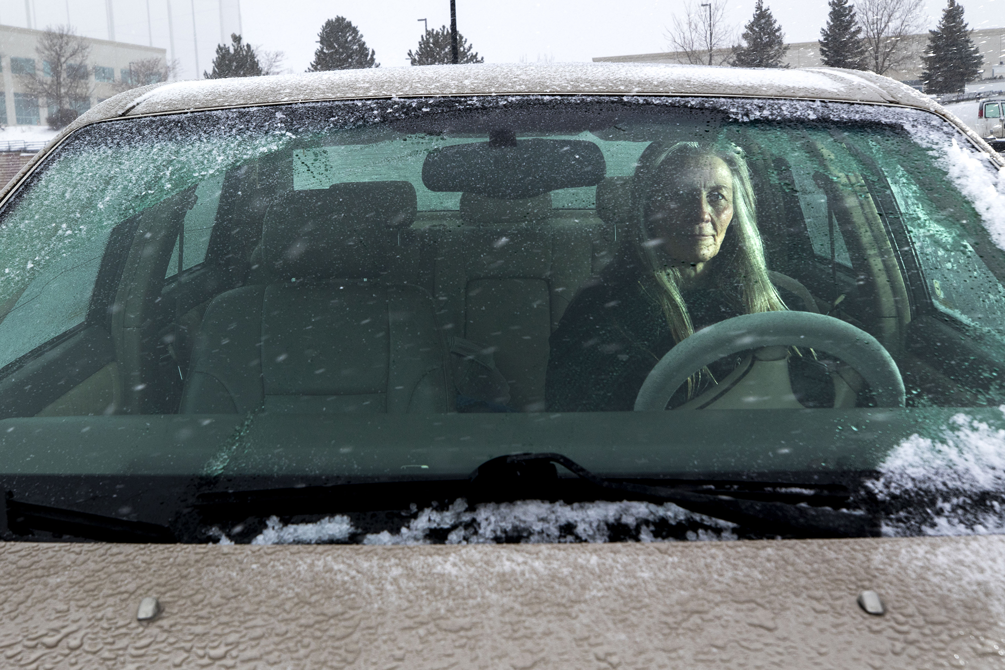Sue Sanders poses for a portrait inside her car, where she sleeps at night in this Centennial Walmart parking lot, Feb. 19, 2020. (Kevin J. Beaty/Denverite)