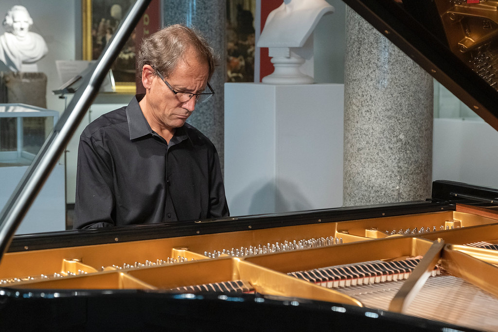David Korevaar sits playing the piano with a classical bust in the background