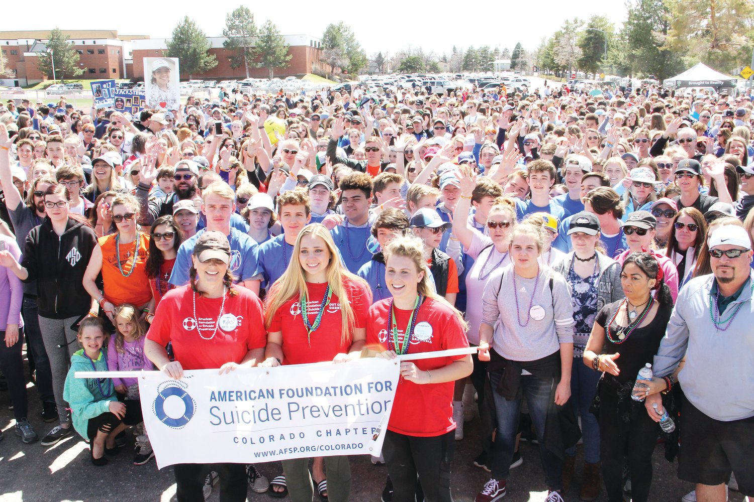 About 1,000 stand behind the organizers of the Out of the Darkness suicide-prevention walk April 14 on the Arapahoe High School campus. In front, left to right, stand Melissa Hughes, a volunteer with the American Foundation for Suicide Prevention, and Brooke and Ry, Arapahoe students.