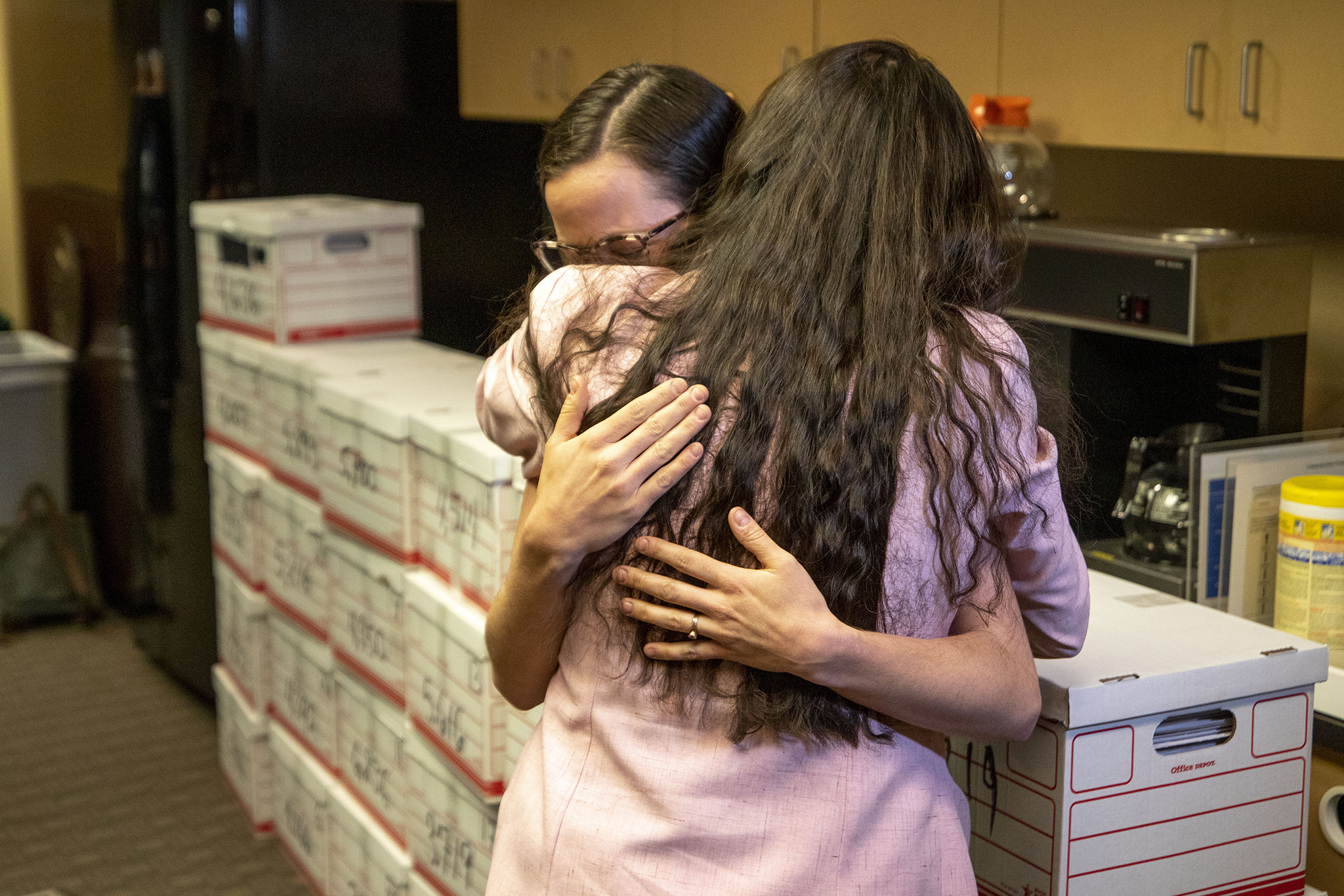 Erin Behrens and Giuliana Day embrace in tears after they helped deliver thousands of signed petitions to the Colorado Secretary of State's office, initiating a ballot measure process that could ban abortions after 22 weeks of pregnancy. March 4, 2020. (Kevin J. Beaty/Denverite)